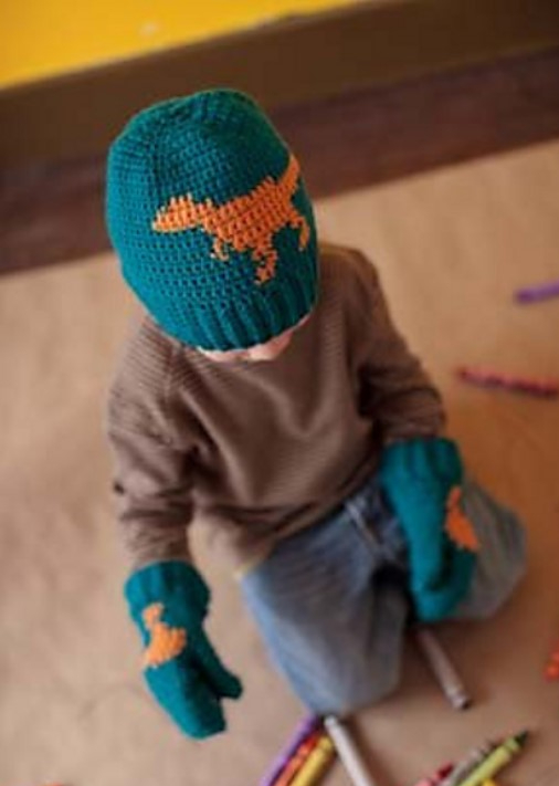 Child wearing a crochet hat and mittens that are teal with an orange t-rex dinosaur on them. The child is on a brown and yellow background and playing with crayons.