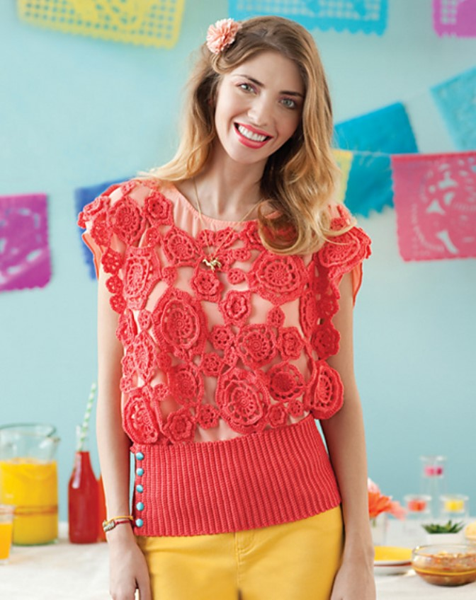 Woman with auburn hair and a peach carnation in her hair. Wearing a dark coral crochet blouse made of many flower motifs over a peach t-shirt. The crochet op has a wide ribbed band at the waist and blue buttons. She is wearing yellow pants. In the background there is a picnic table and a light blue wall with colorful garlands of pendants.