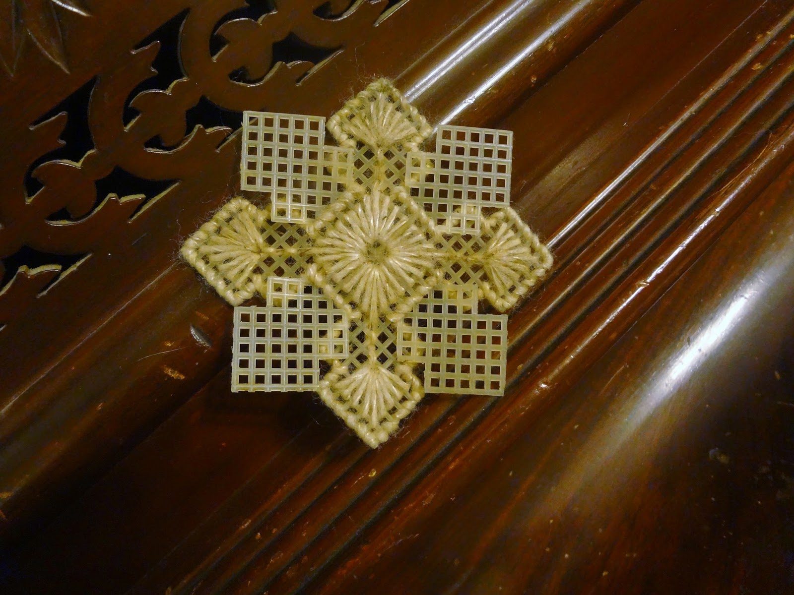Needlepoint snowflake on a wooden background found in the debris of the 2013 Moore, Oklahoma tornado.
