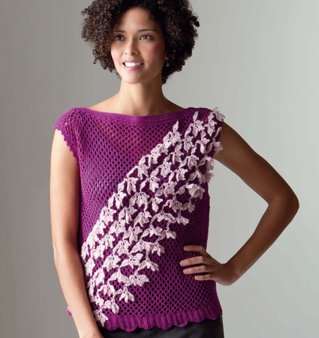 Woman wearing a fuchsia crochet top with diagonal rows of crochet lace trim across the front.