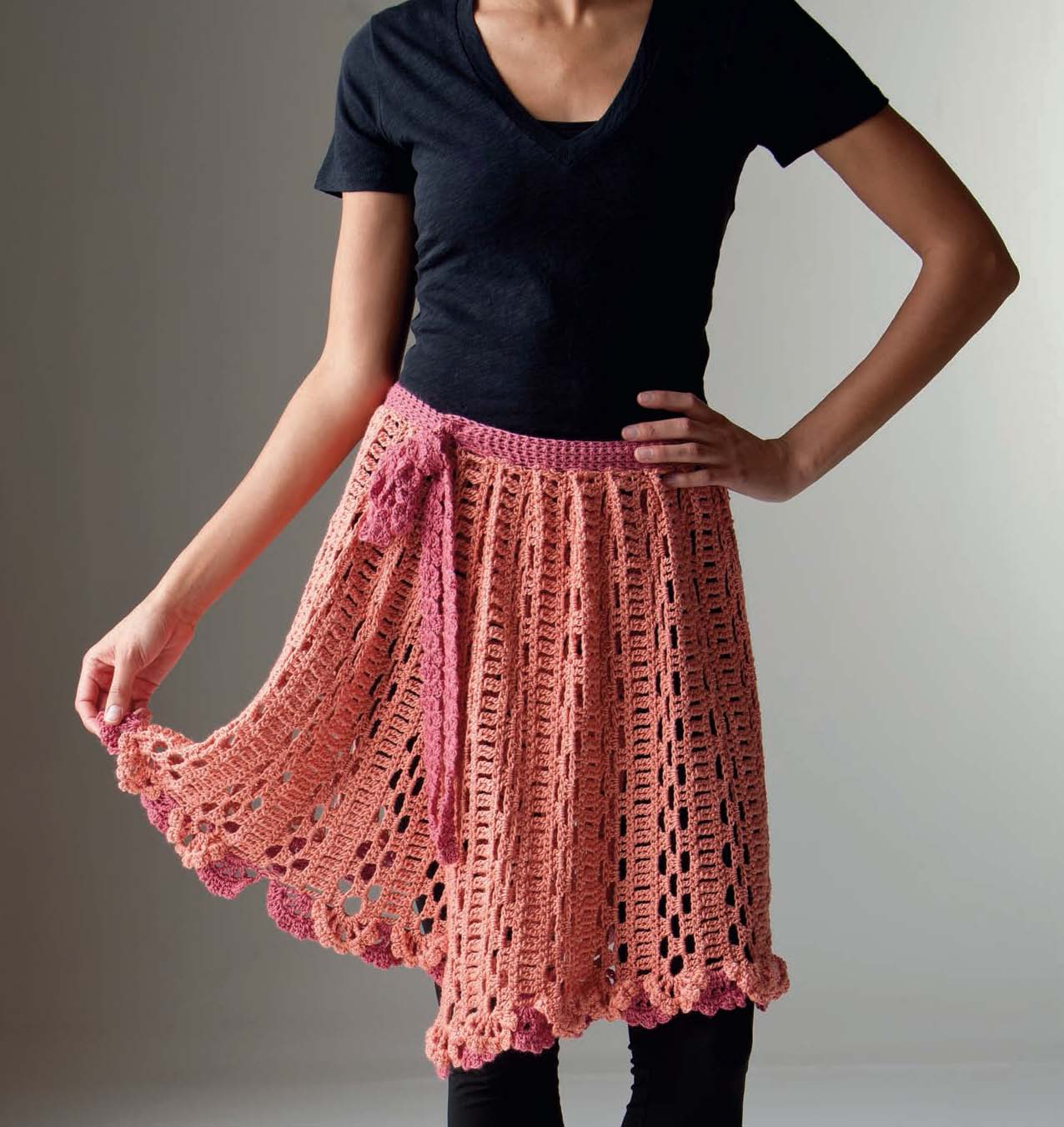 Woman wearing a black t-shirt and leggings and a crochet lace skirt in orange and pink.