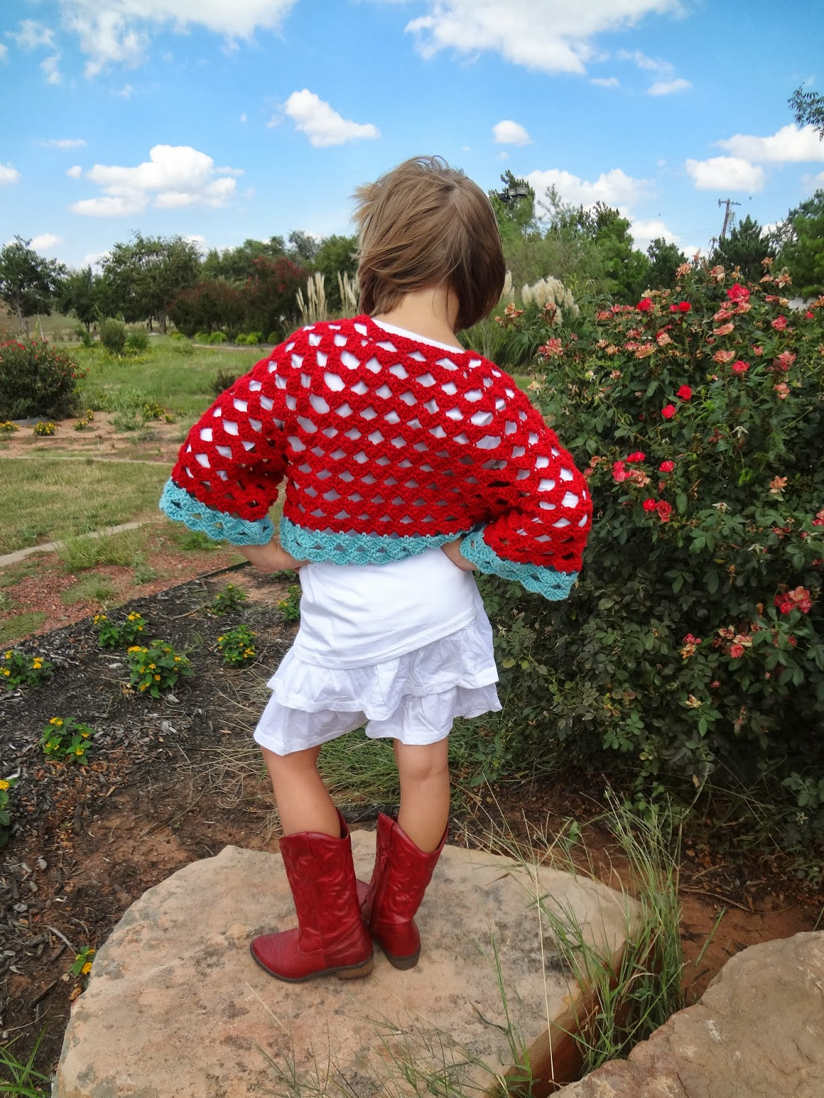 Back view of a red and aqua crochet cardigan on a young girl standing in a garden.