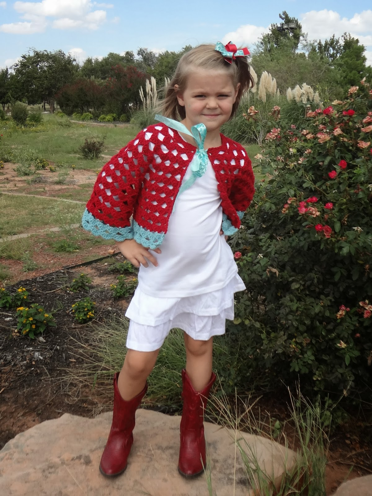 Young girl wearing an openwork crochet cardigan, white t-shirt and skirt, and red boots standing in a garden.