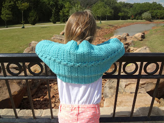 Girl standing at a rail with her back to the camera, wearing a crochet cabled shrug. Free crochet pattern from Banana Moon Studio.