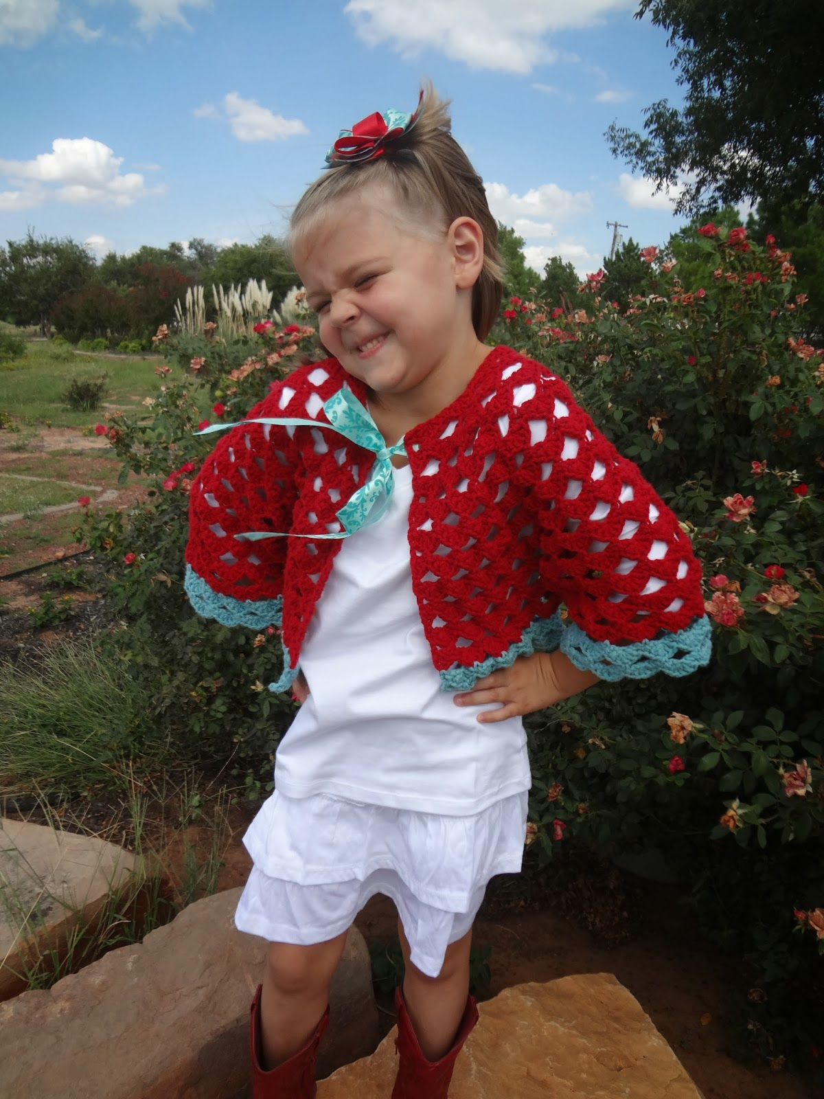 Little girl wearing a crochet cardigan in red and aqua. Free crochet girl's cardigan pattern from Banana Moon Stuido.