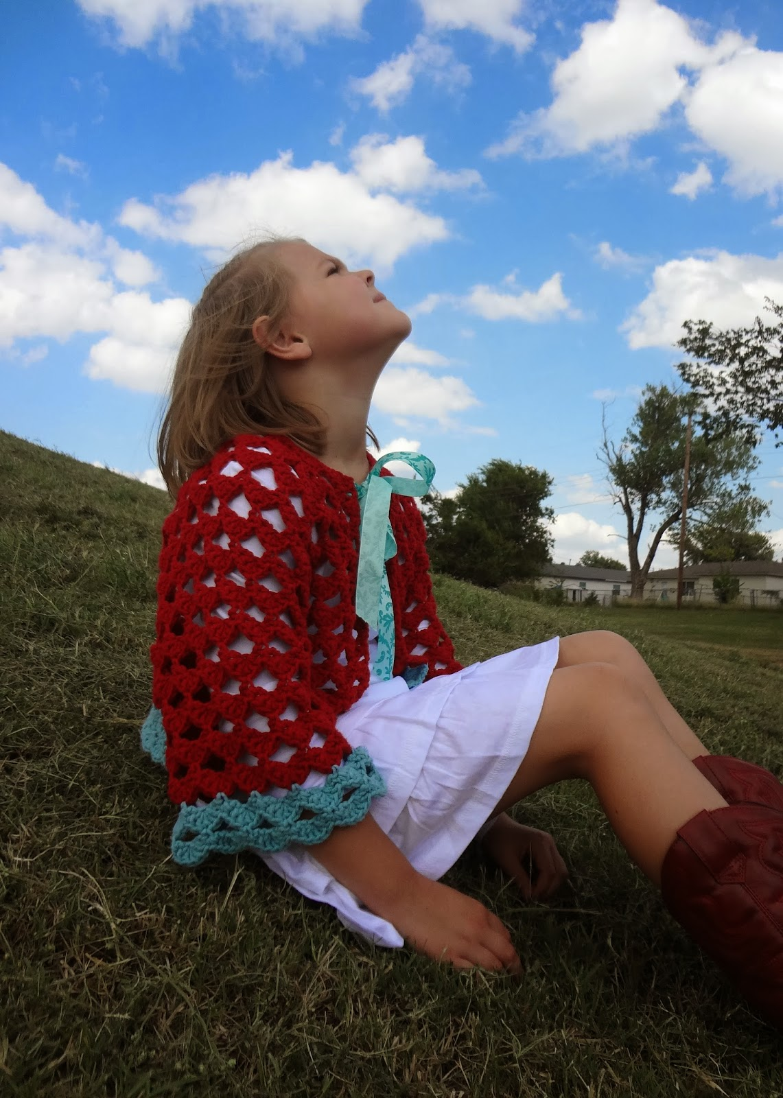 Girl sitting on a hill looking up at the sky. She's wearing a red and aqua crochet cardigan with a bow. Free crochet pattern from Banana Moon Studio.