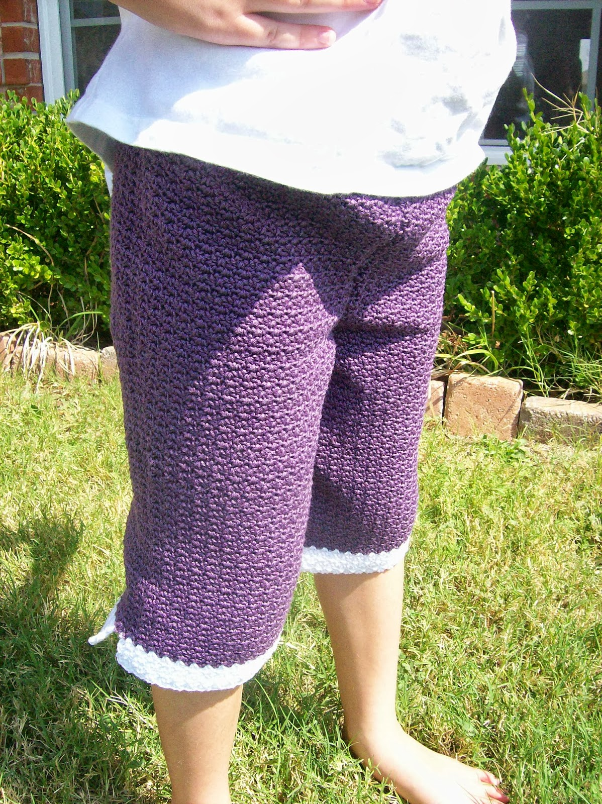 Child wearing purple crochet capri pants and standing barefoot in the grass in front of a flower bed.