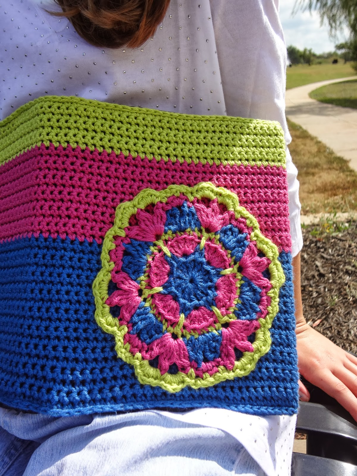 Green, pink, and blue crochet motif on a crochet book cover. Free pattern from Banana Moon Studio.