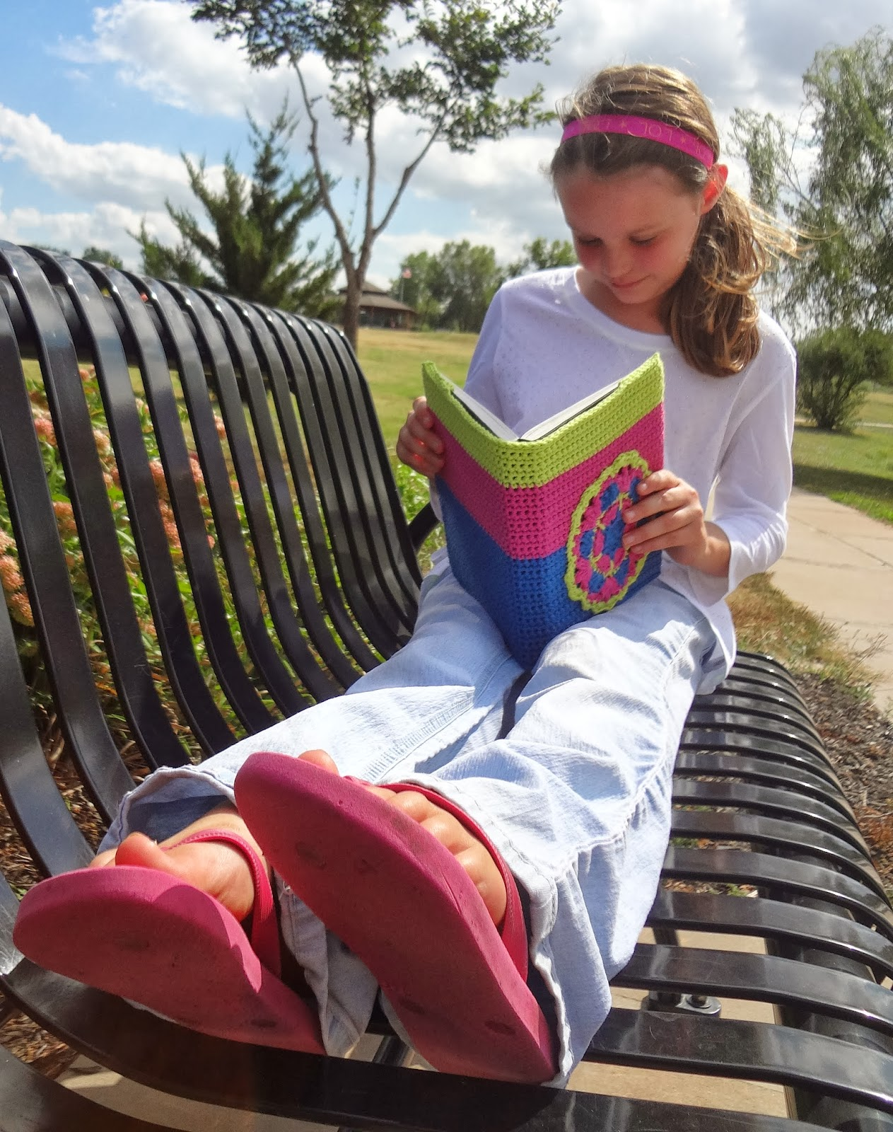 Girl sitting on a park bench reading a book that has a green, pink, and blue crochet cover on it with a mandala. Free crochet pattern from Banana Moon Studio.