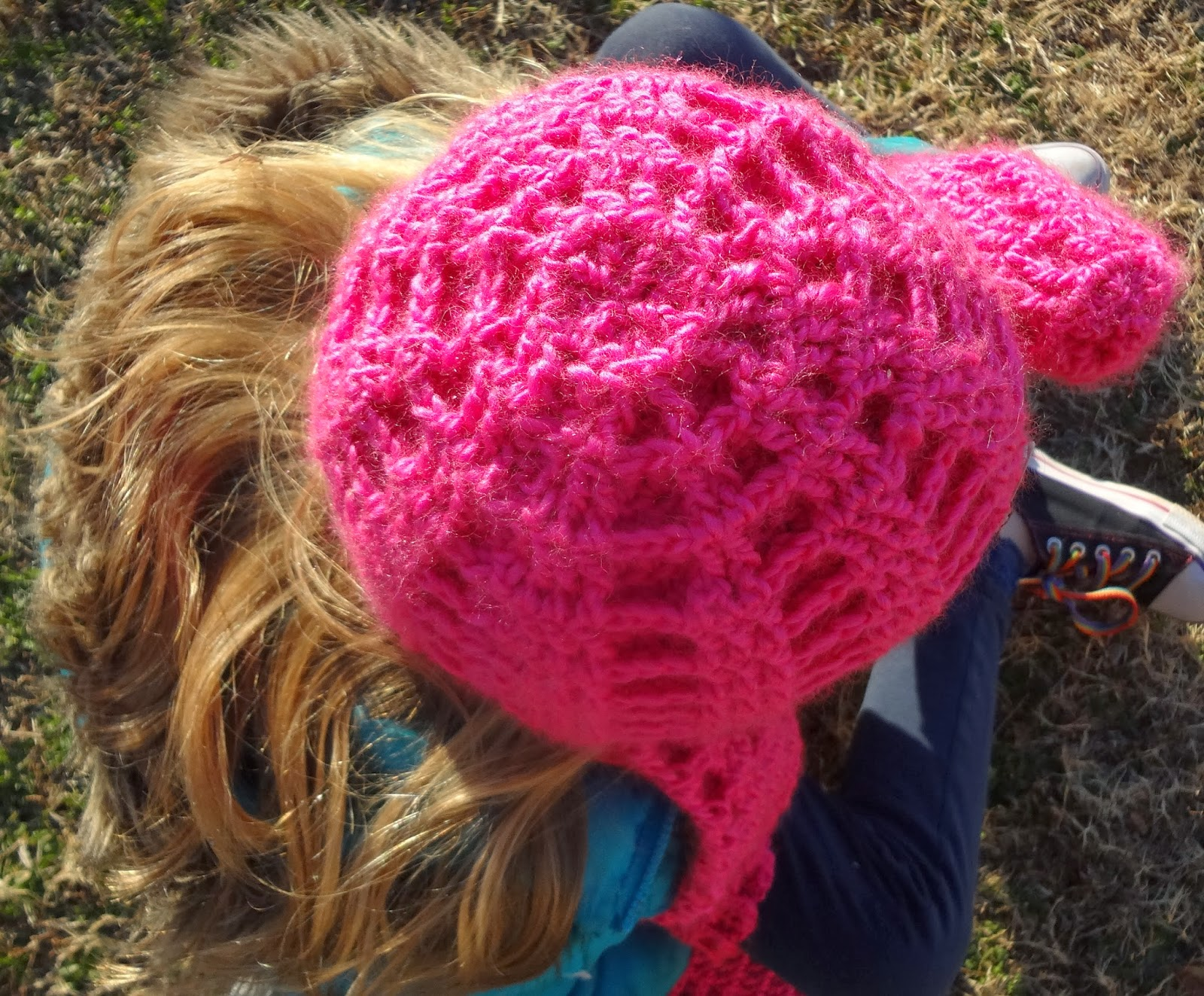 Looking down at the top of a crochet hat in hot pink with matching scarf and mittens.