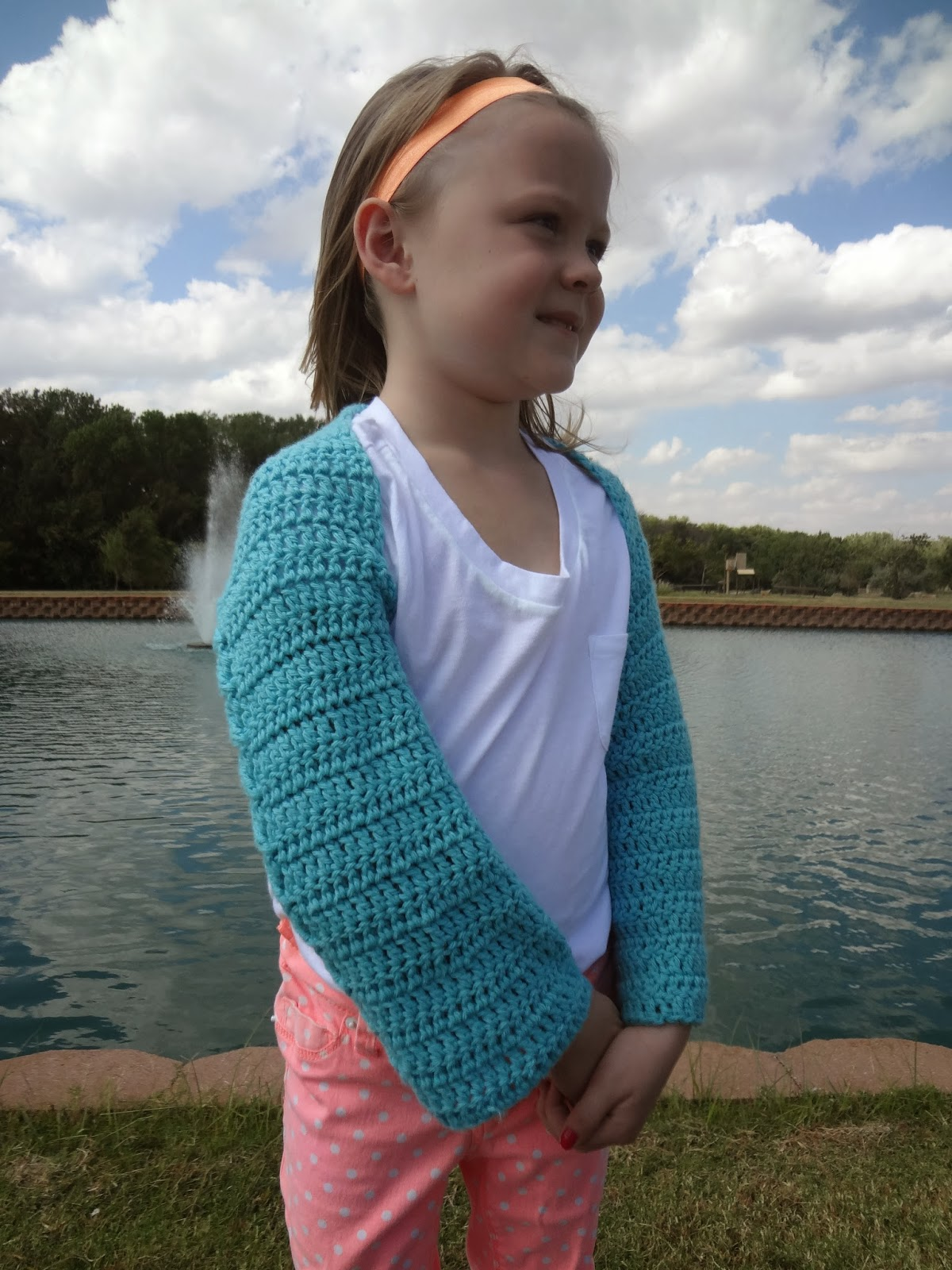 Child wearing a turquoise crochet shrug, white t-shirt, and orange pants standing in front of a pond with fountain. Free crochet pattern.