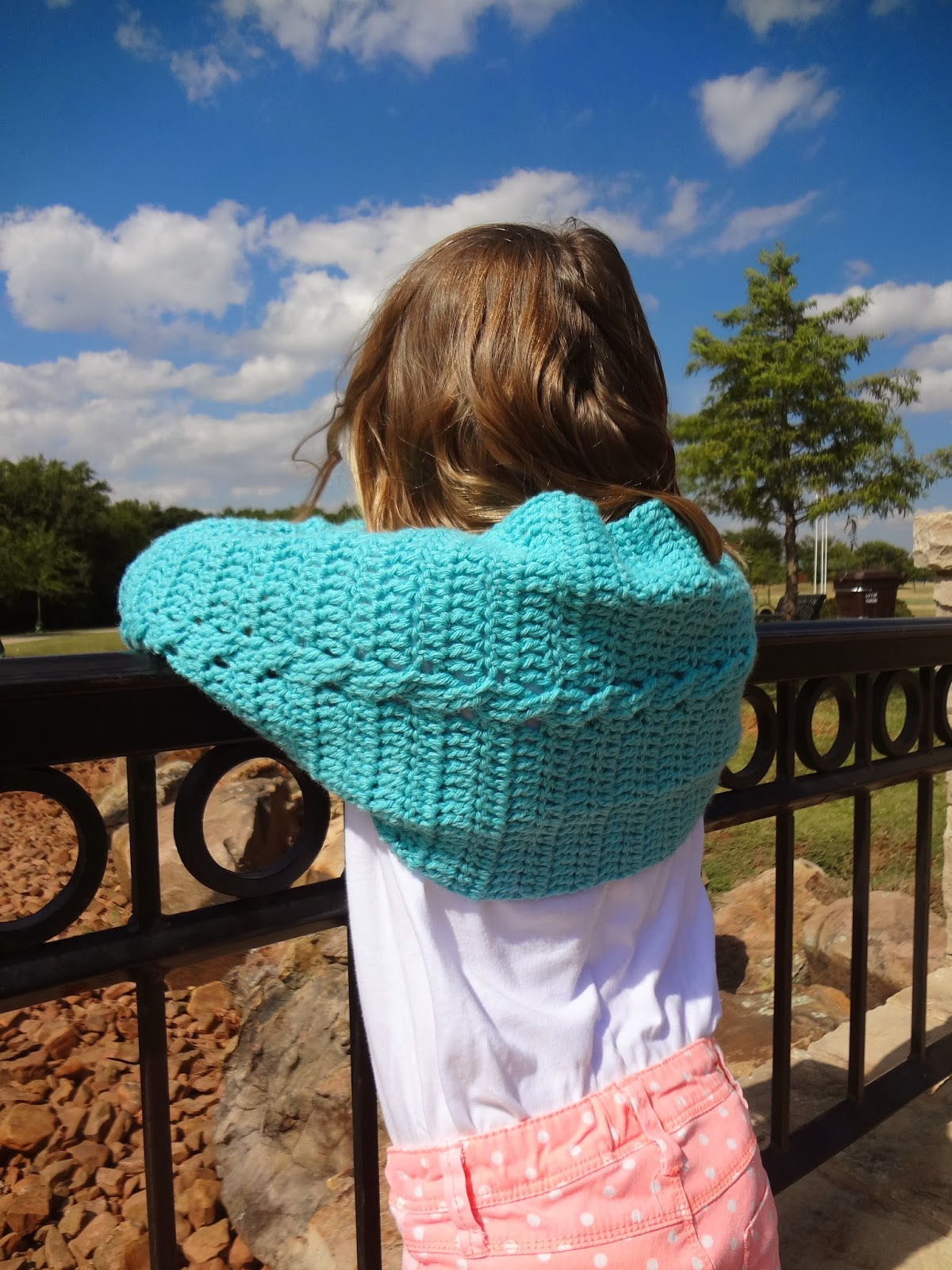 Girl wearing a turquoise cabled crochet shrug and standing in front of an iron railing. Free crochet pattern.