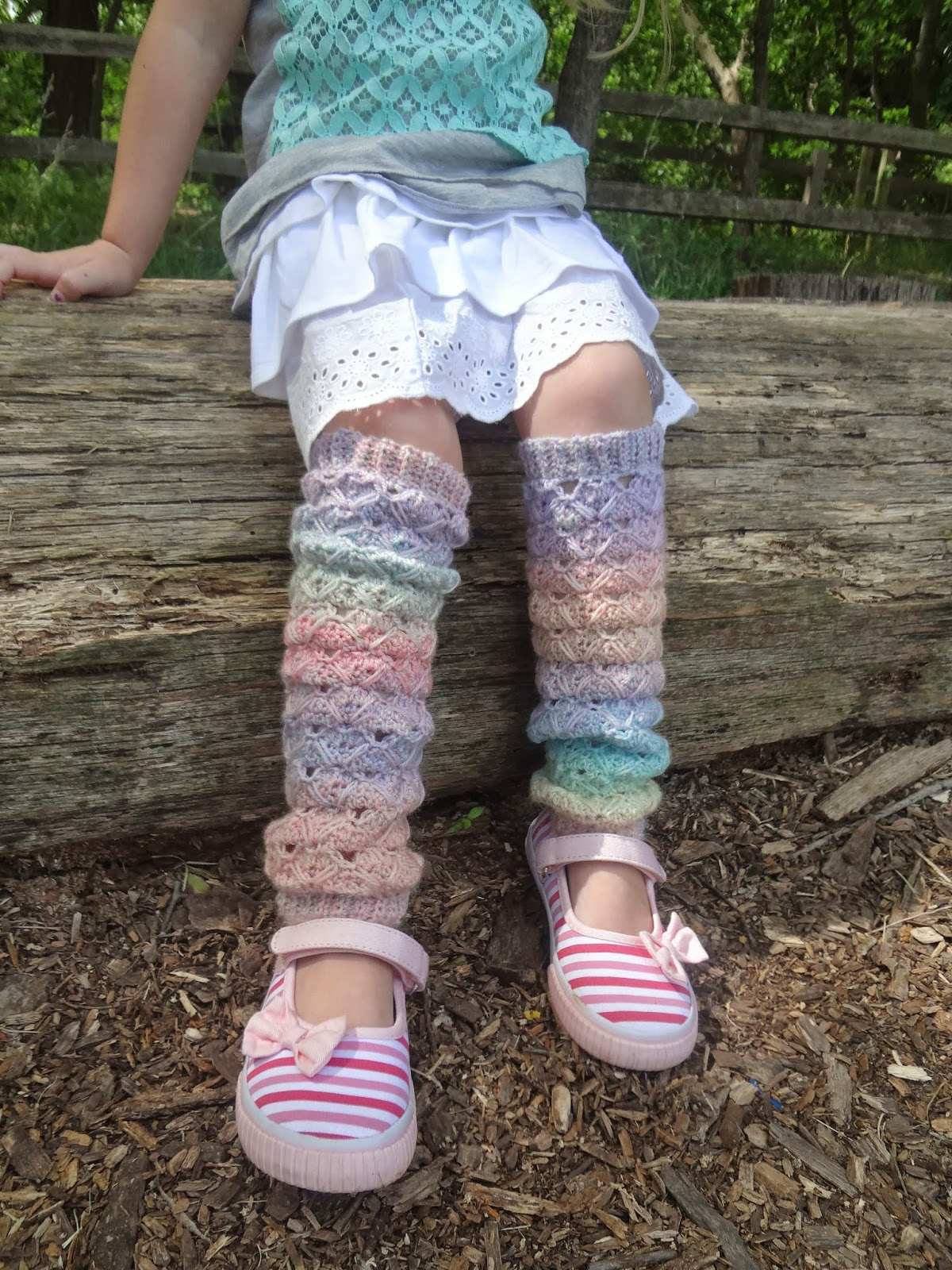 Child wearing rainbow crochet leg warmers at the park. Free crochet pattern for children from Banana Moon Studio.