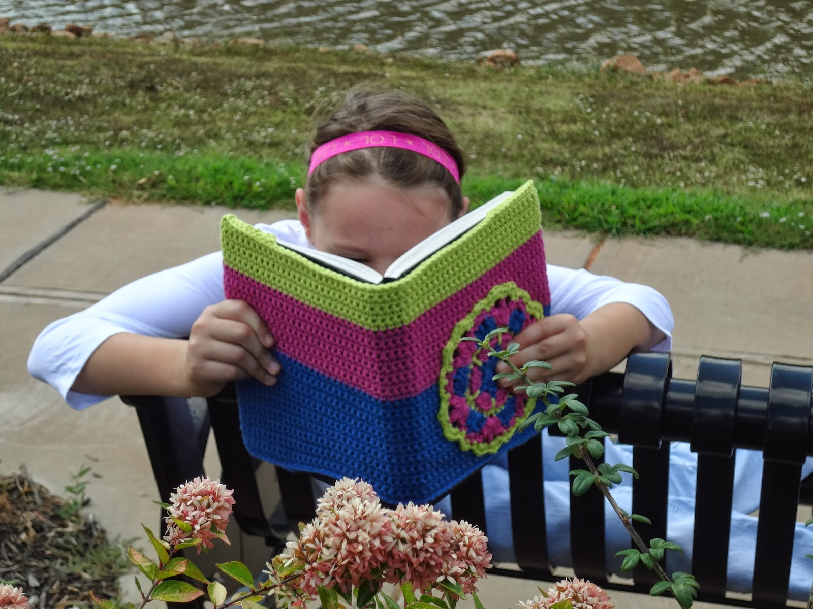 Girl sitting on a park bench reading a book with a crochet cover on it. Free crochet book cover pattern from Banana Moon Studio.