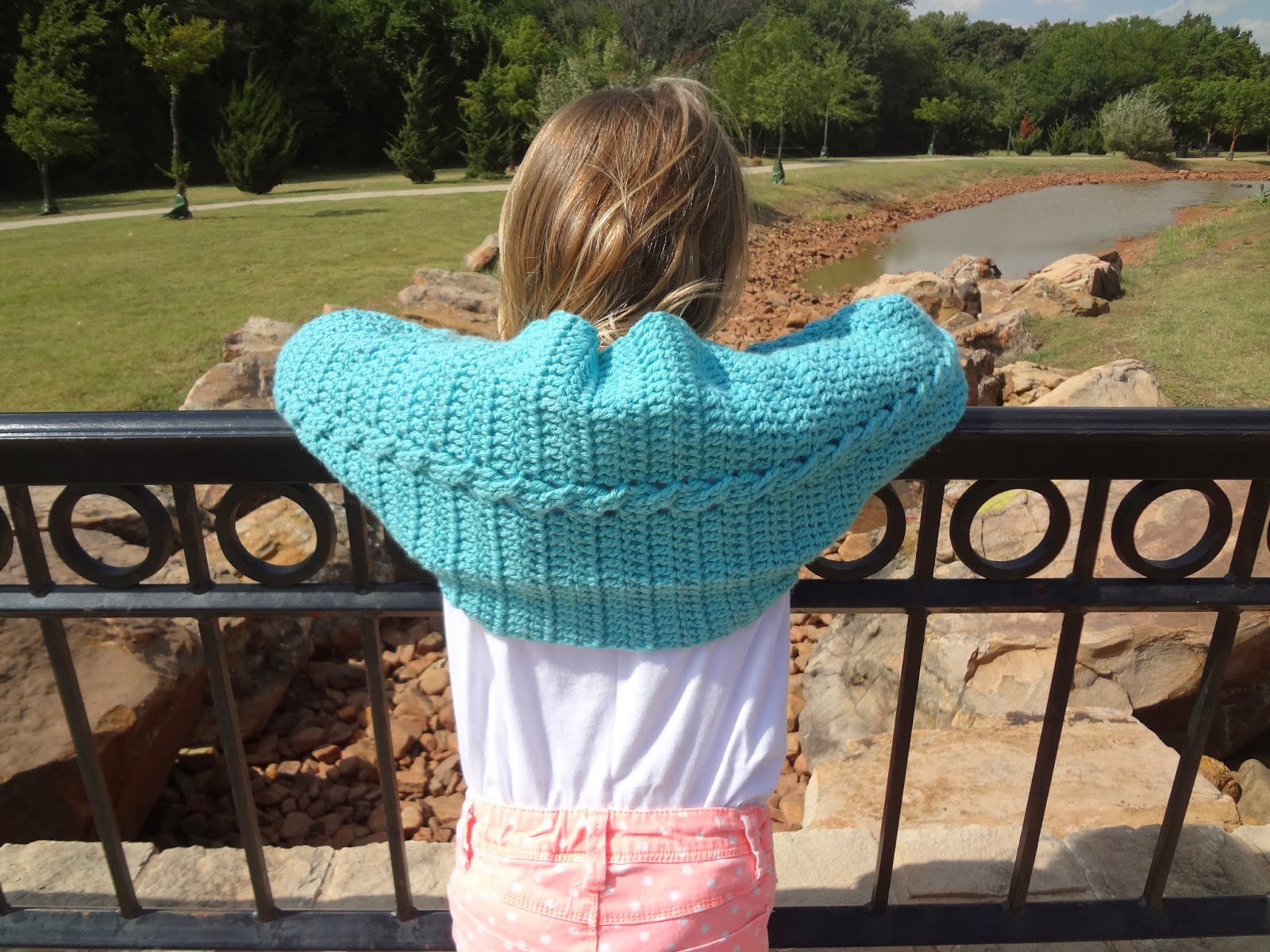 Child wearing a turquoise crochet cabled shrug and standing in front of an iron fence with a stream in the background. Free crochet pattern!
