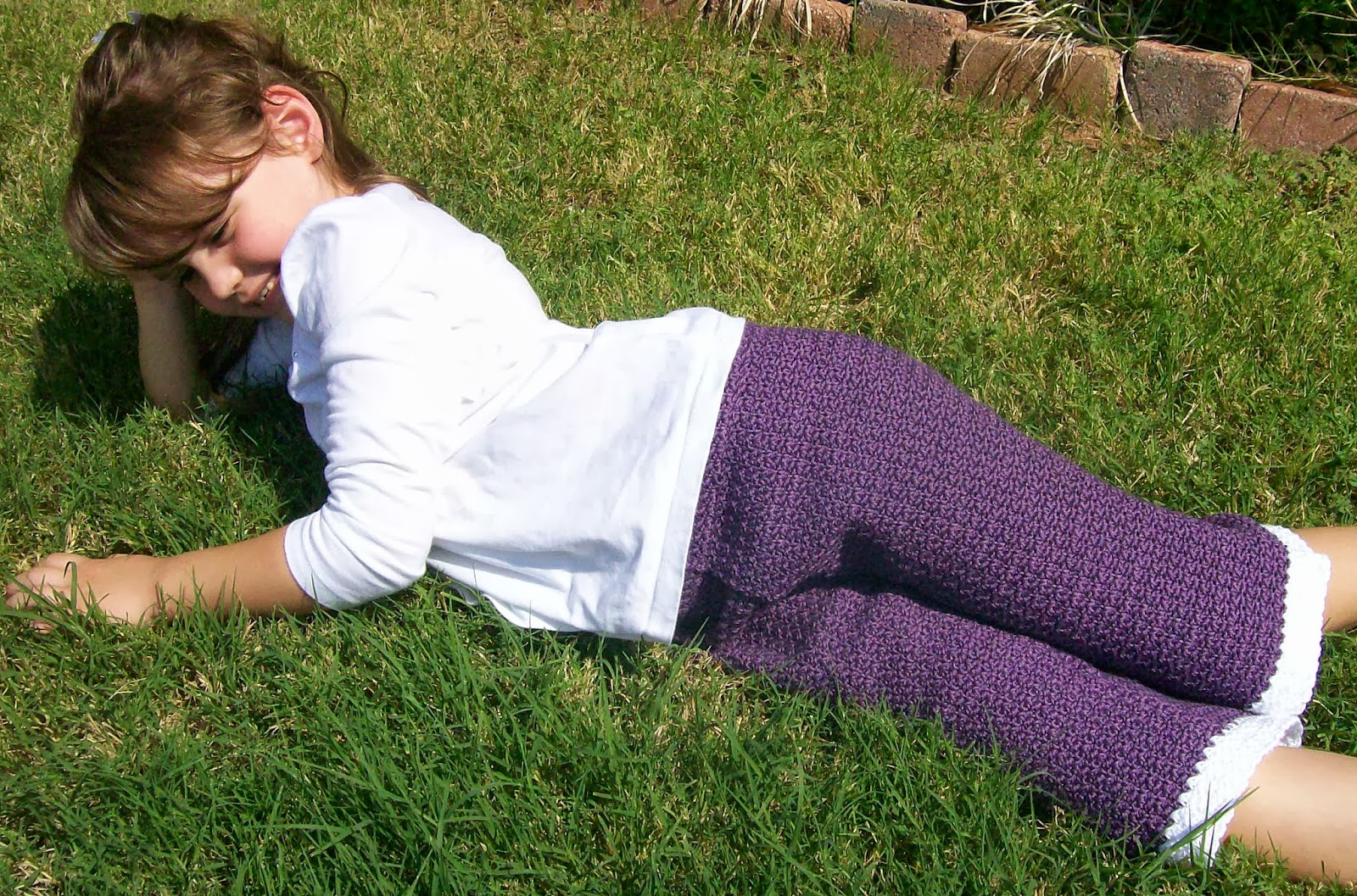 Child laying down in the grass wearing a white shirt and purple crochet capri pants.