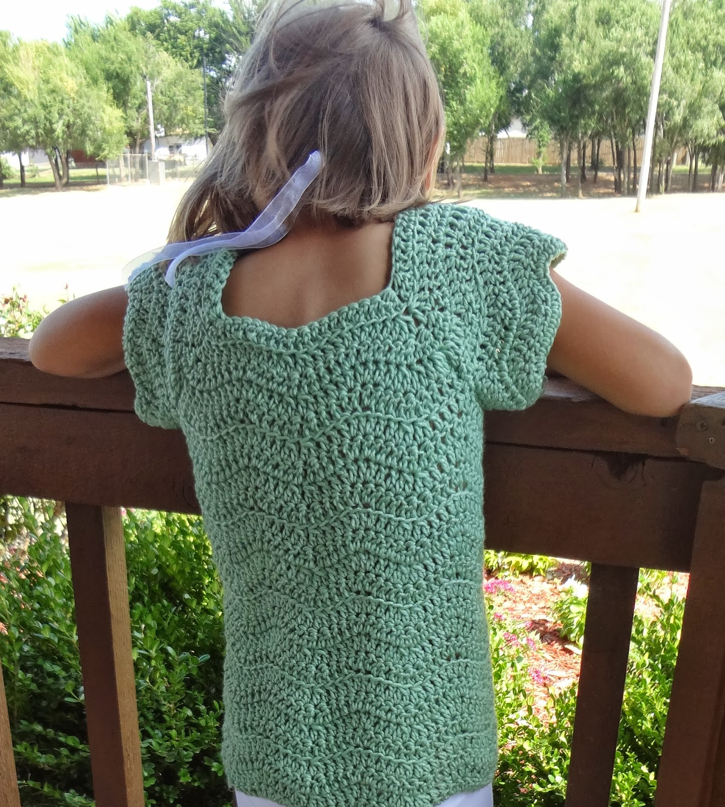 Girl wearing a ripple stitch crochet top with short sleeves standing at a rale in a gazebo. Crochet pattern from Banana Moon Studio.