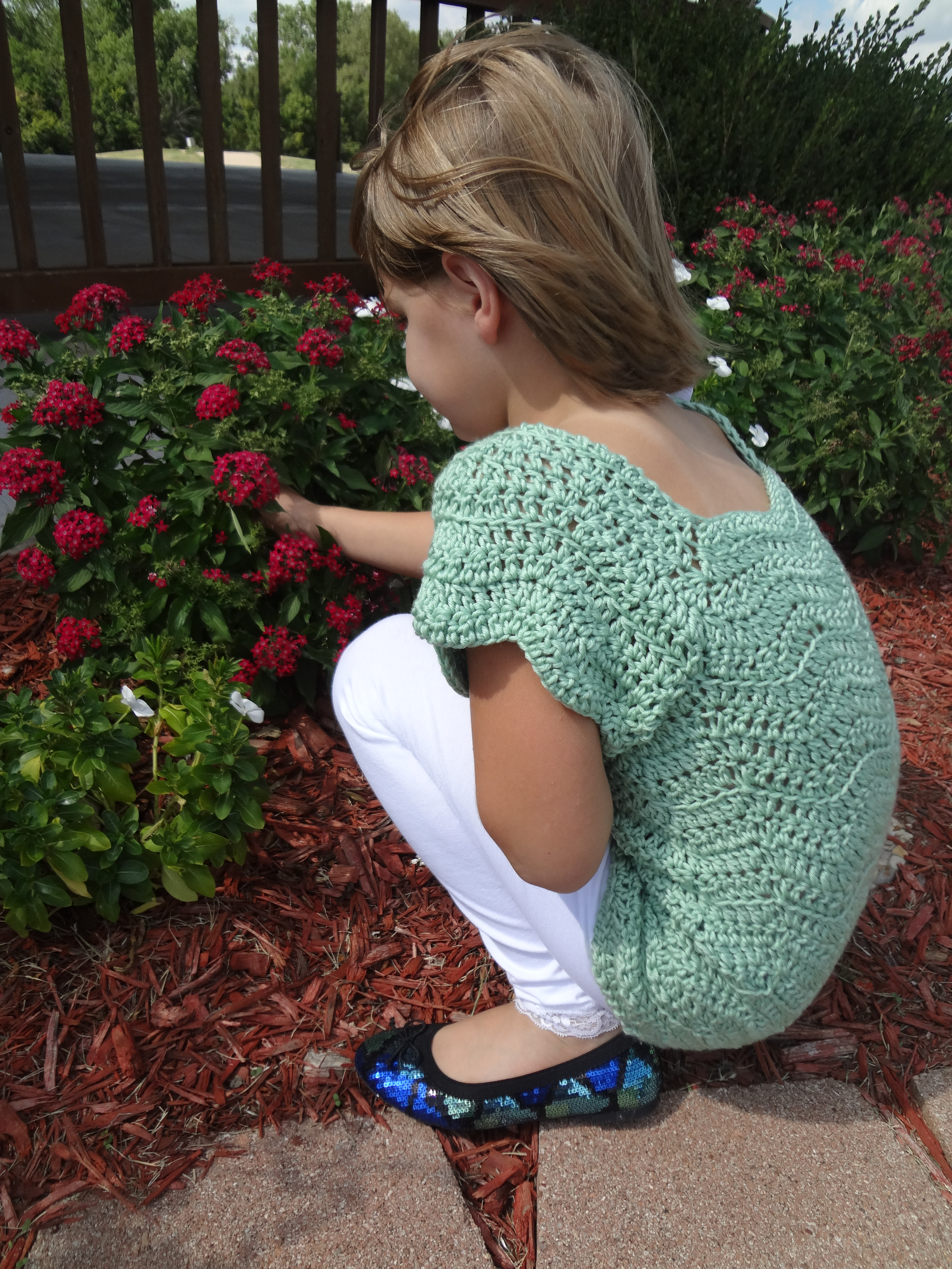Girls wearing a crochet op and white pants with sequin shoes looking at flowers in a garden.