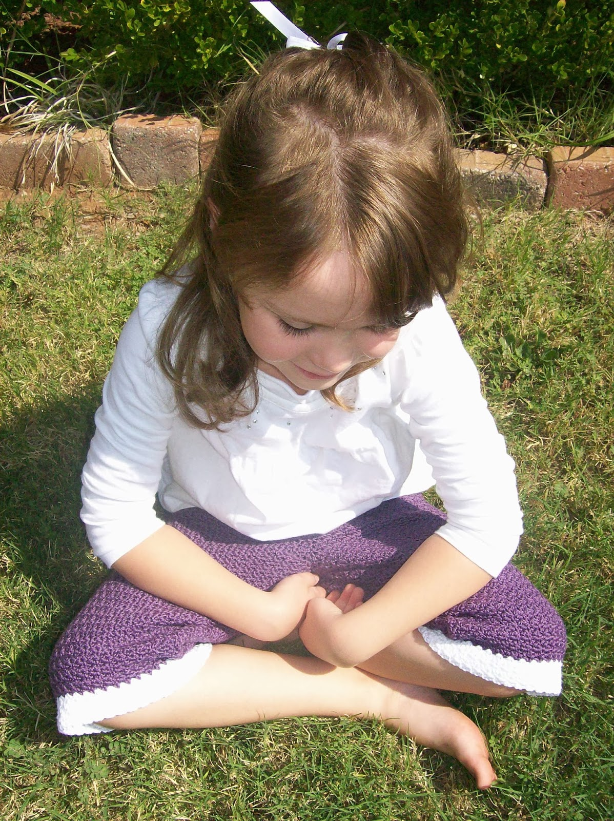 Girl sitting in the grass wearing a white shirt and purple crochet capri pants. Crochet pattern from Banana Moon Studio.