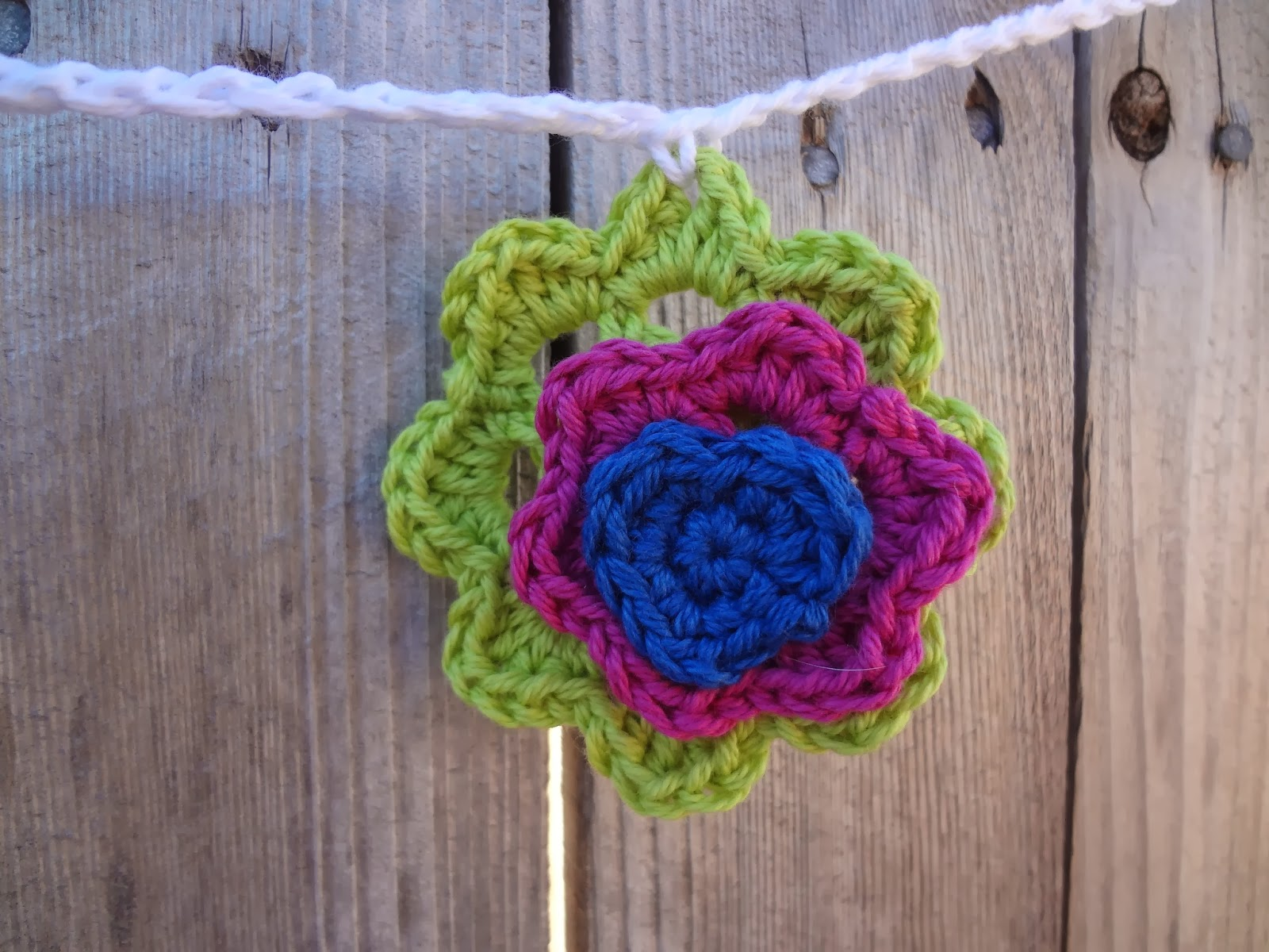 Layered crochet flower in bright green, fuchsia, and cobalt blue, attached to a white string as part of a garland.