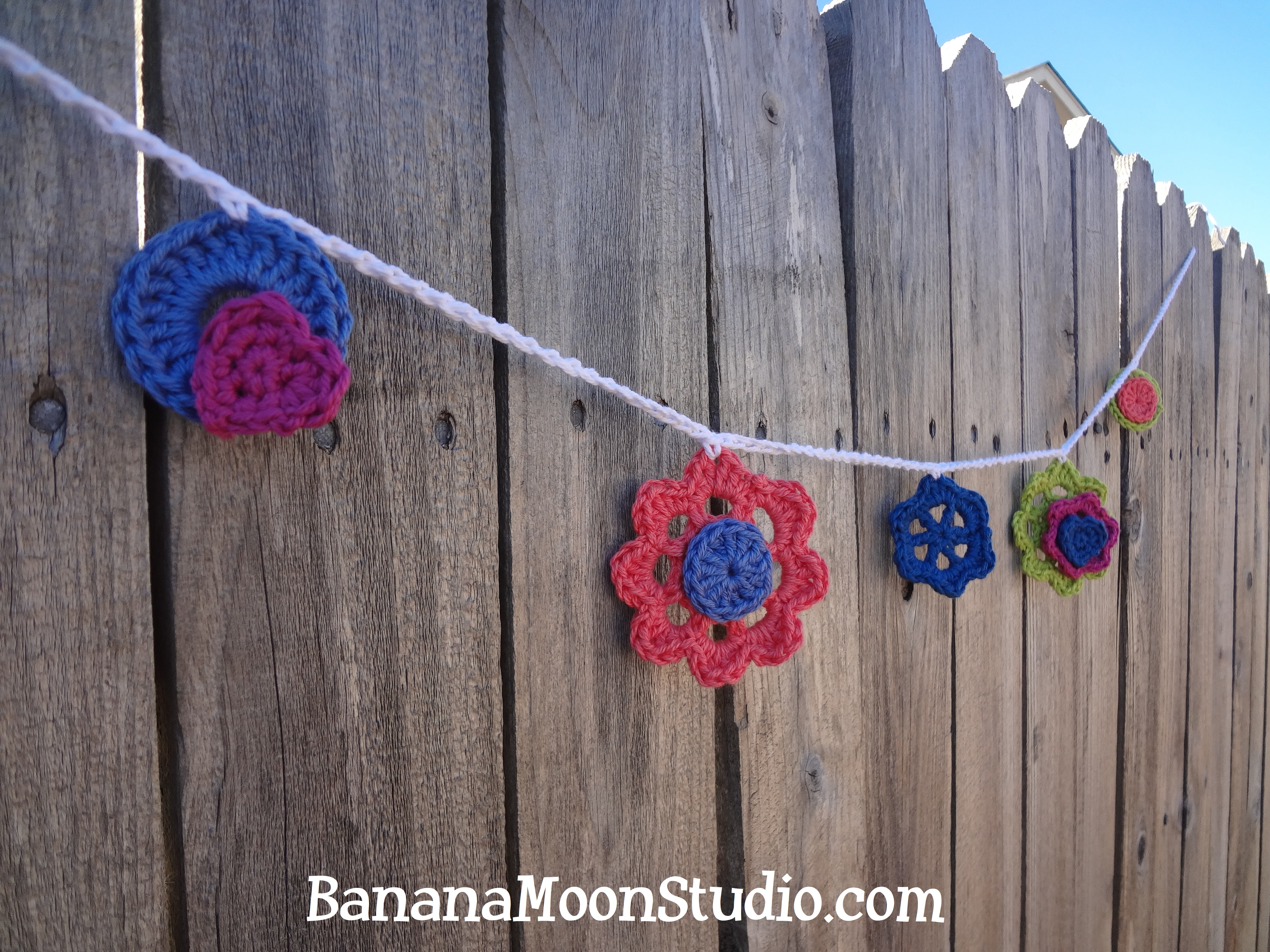 Crochet flowers and other small motifs on a white chain with a wooden fence behind it. Gardens Galore Garland, free crochet pattern for a floral spring garland, from Banana Moon Studio