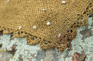 Close up of a golden metalic crochet shawl with silver charms on it and a lace edging. It's on top of a lichen-covered rock.