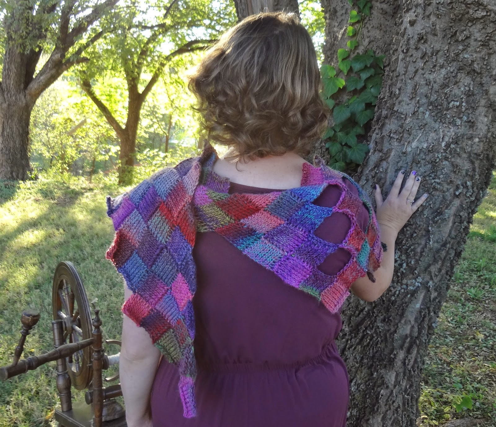Woman wearing the Tunisian crochet entrelac On Fire Wrap and maroon dress, standing in the woods.