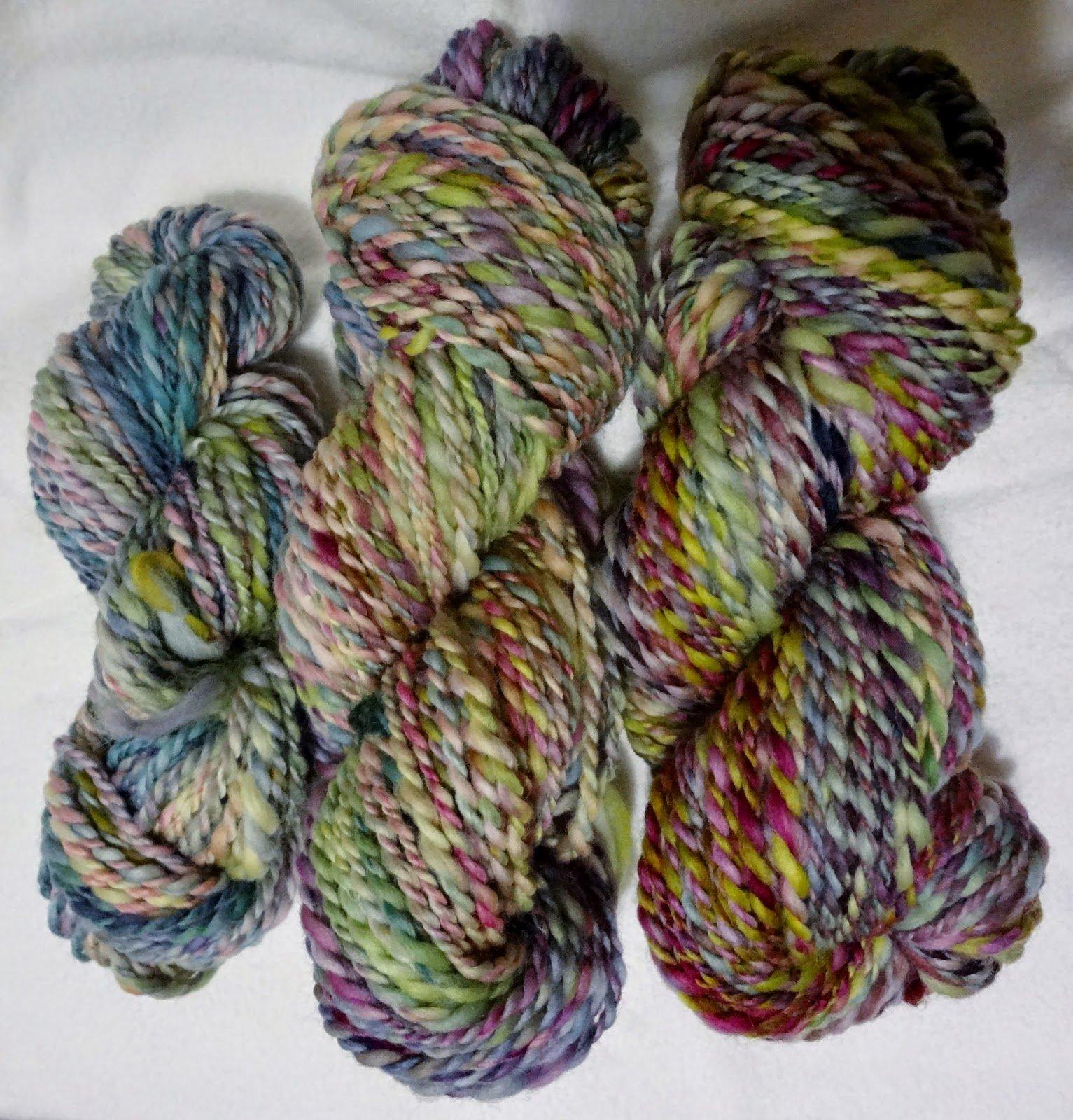 Three skeins of handspun yarn on a white background.
