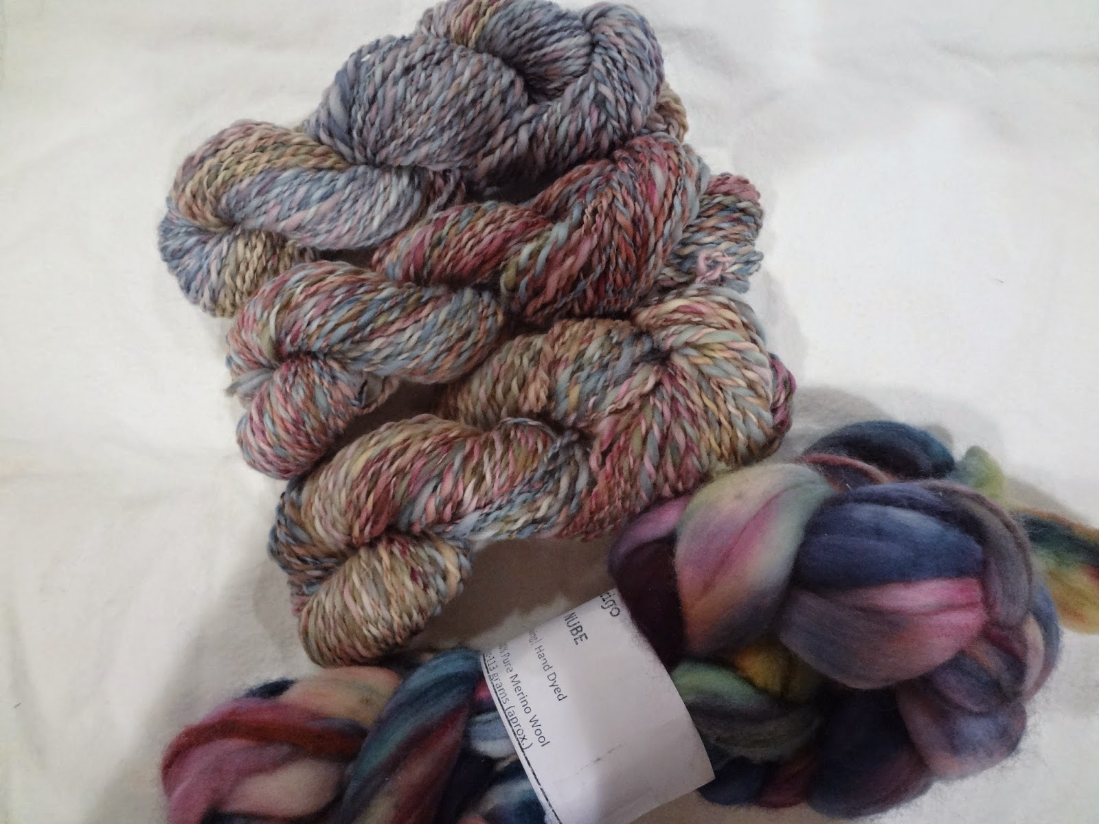 Three skeins of handspun yarn and a bundle of roving on a white background.