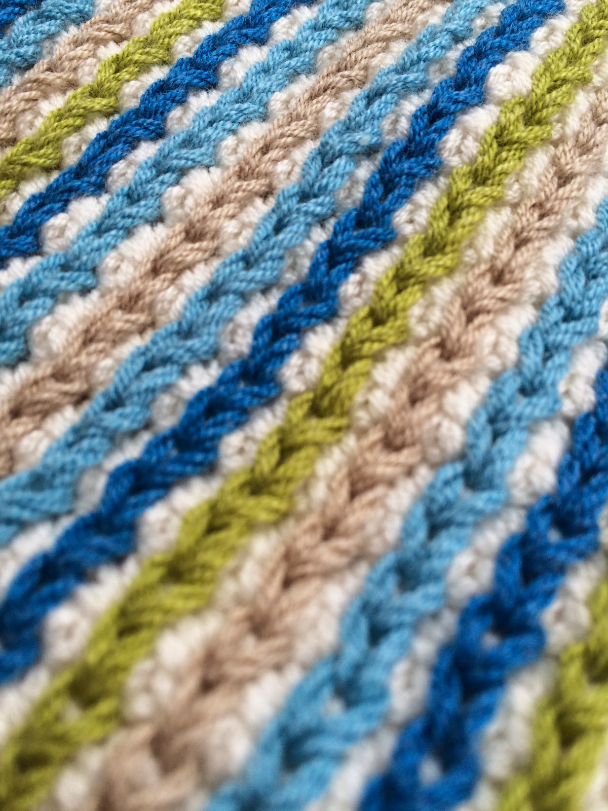 Close up of crochet fabric with surface slip stitches in tan, green, and two shades of blue.