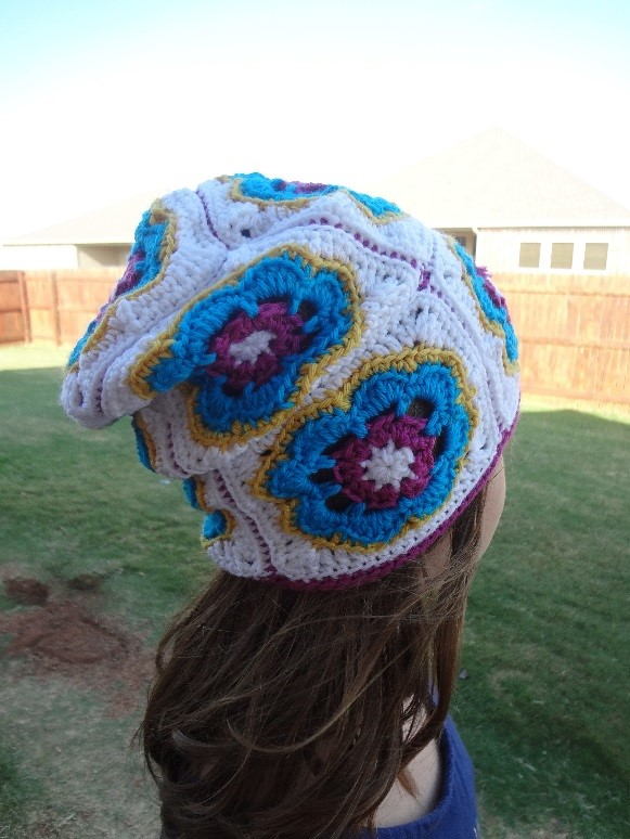 Young girl in a fenced yard wearing a brightly colored crochet hat made of flowered motifs. In this back view we can see that the hat is slouchy.