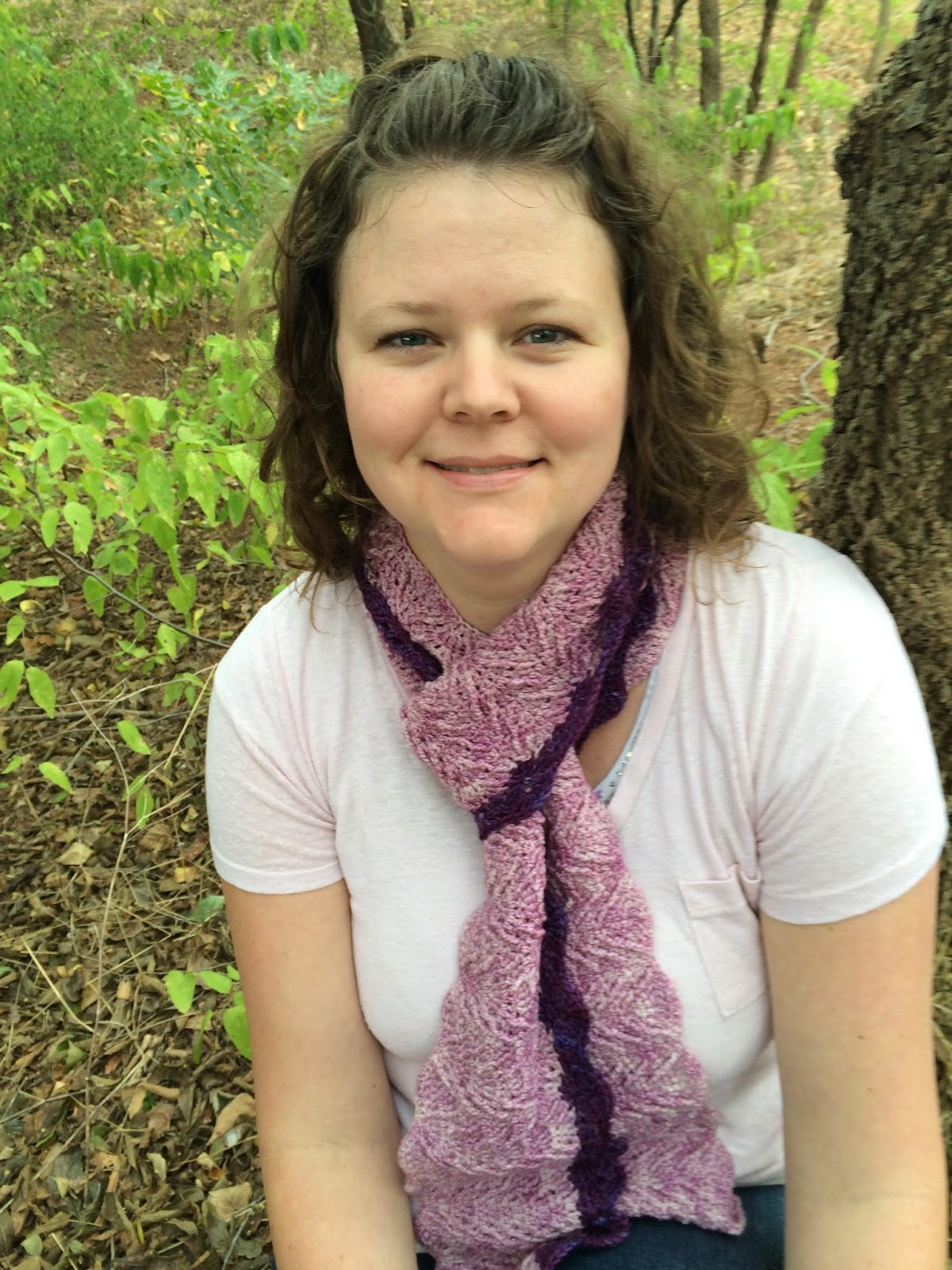 Woman in the woods wearing a purple crochet textured scarf.