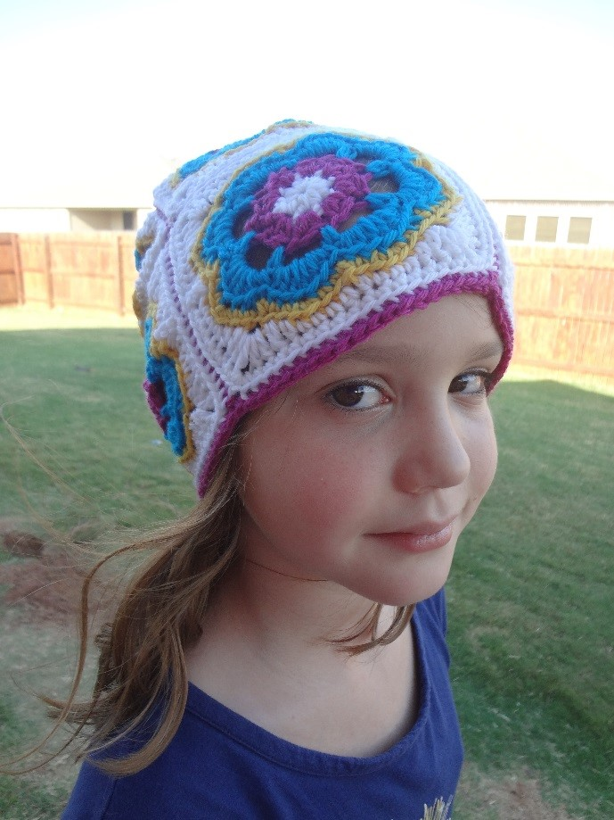 Young girl in a fenced yard wearing a brightly colored crochet hat made of flowered motifs.