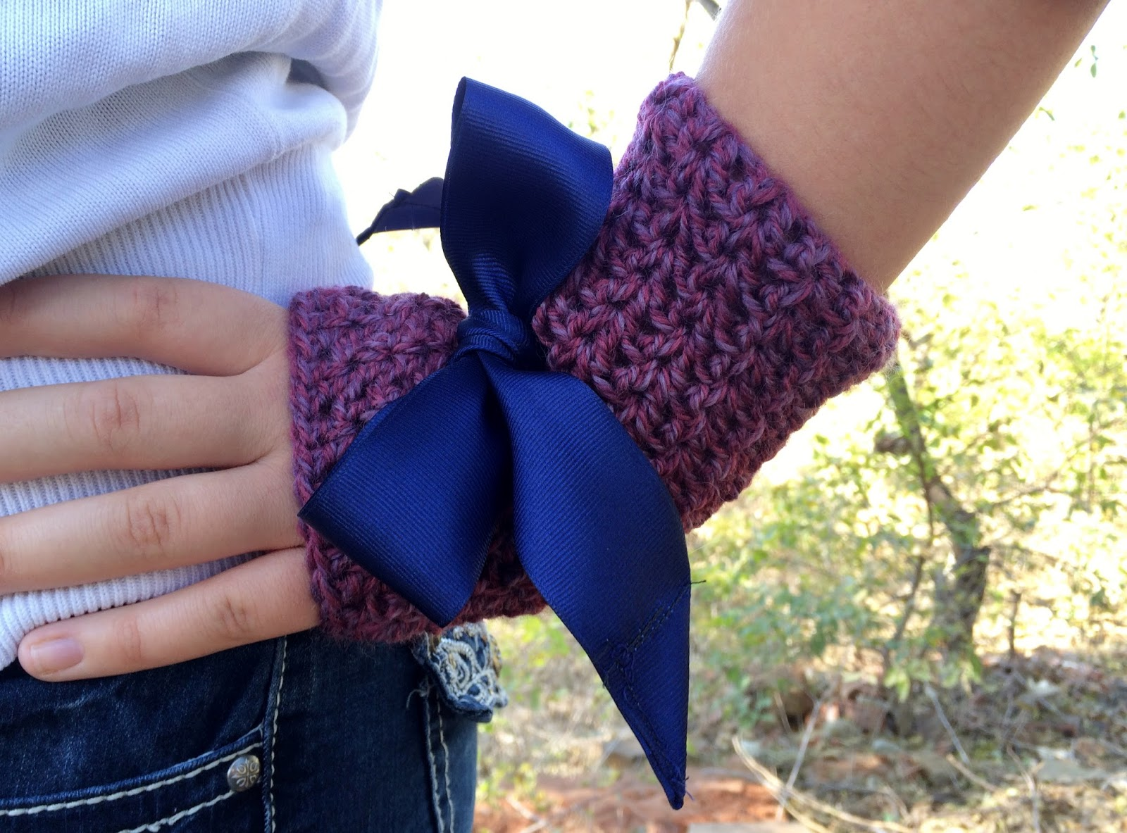 Hand wearing a mauve crochet fingerless glove with a large royal blue ribbon bow. Hand is on the hip.