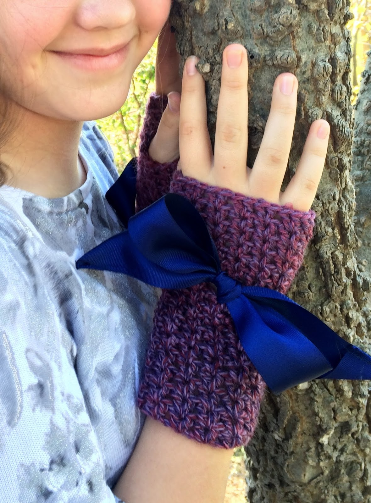 Teenage girls standing next to a tree with hands on the tree wearing mauve crochet fingerless gloves with large navy blue ribbon bows.