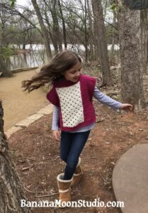 Girl playing at a park and wearing a fuchsia and white poncho with a center lace panel.