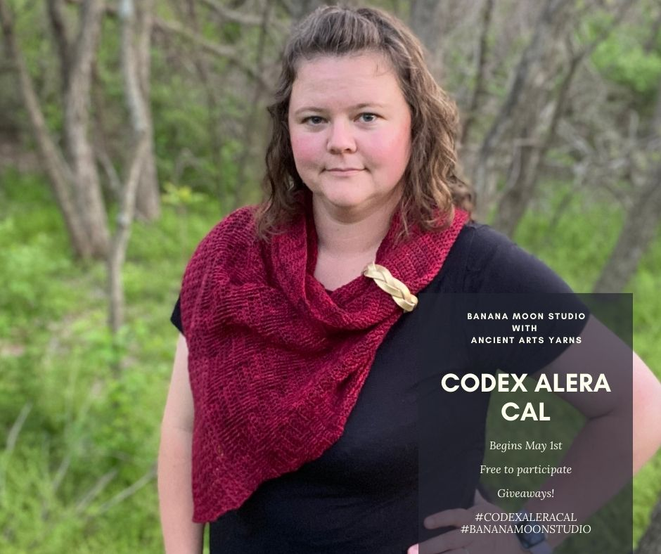Woman standing in the woods wearing a black t-shirt and red crochet shawl with a gold-colored braided leather shawl cuff. Text reads: Banana Moon Studio with Ancient Arts Yarn. Codex Alera CAL. Begins May 1st. Free to participate. Giveaways! #codexaleracal #bananamoonstudio