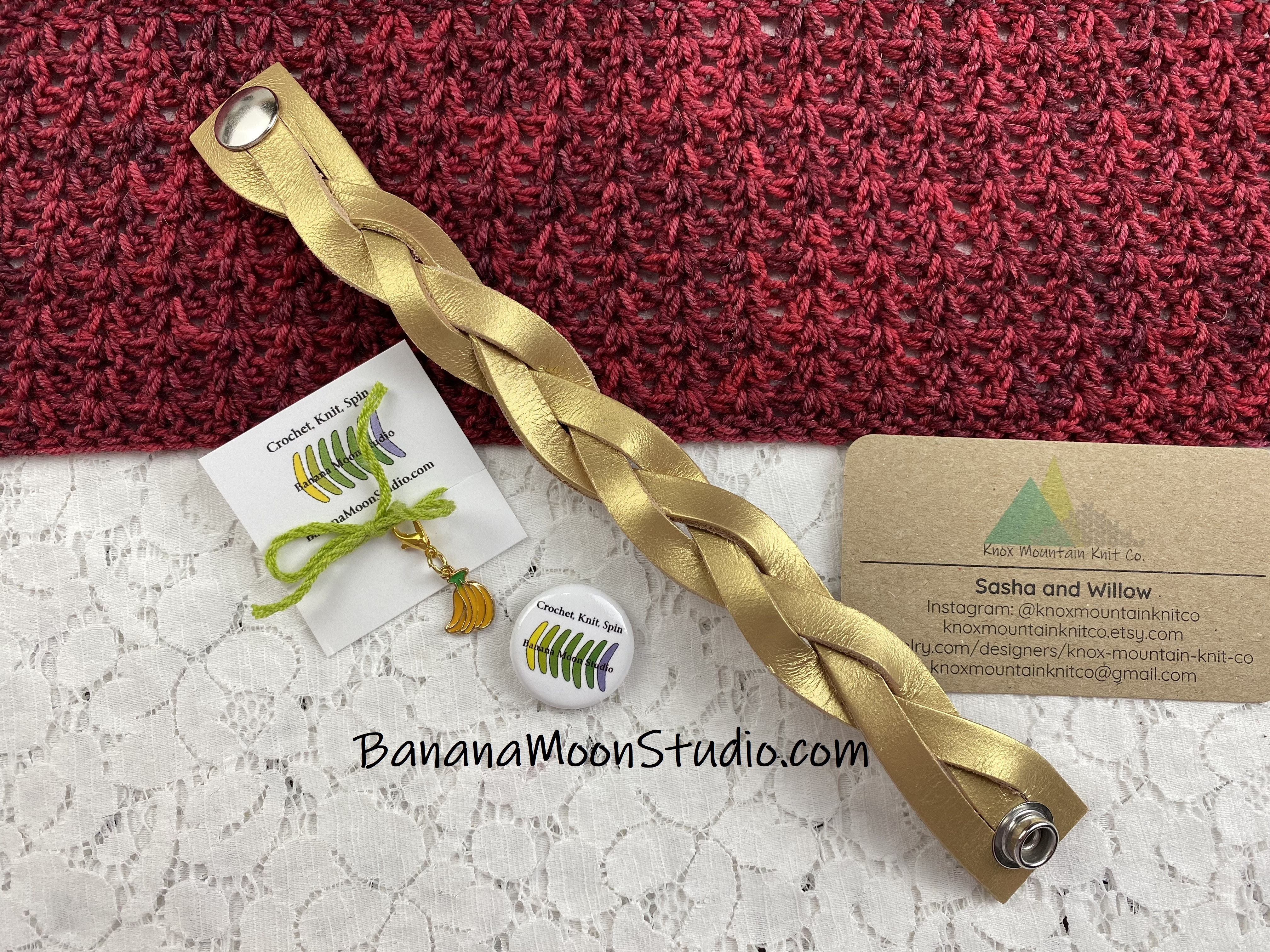 Edge of a red crochet shawl, gold braid leather shawl cuff, Banana Moon Studio stitch marker and button, business card for Knox Mountain Knit Co. on a white lace background.