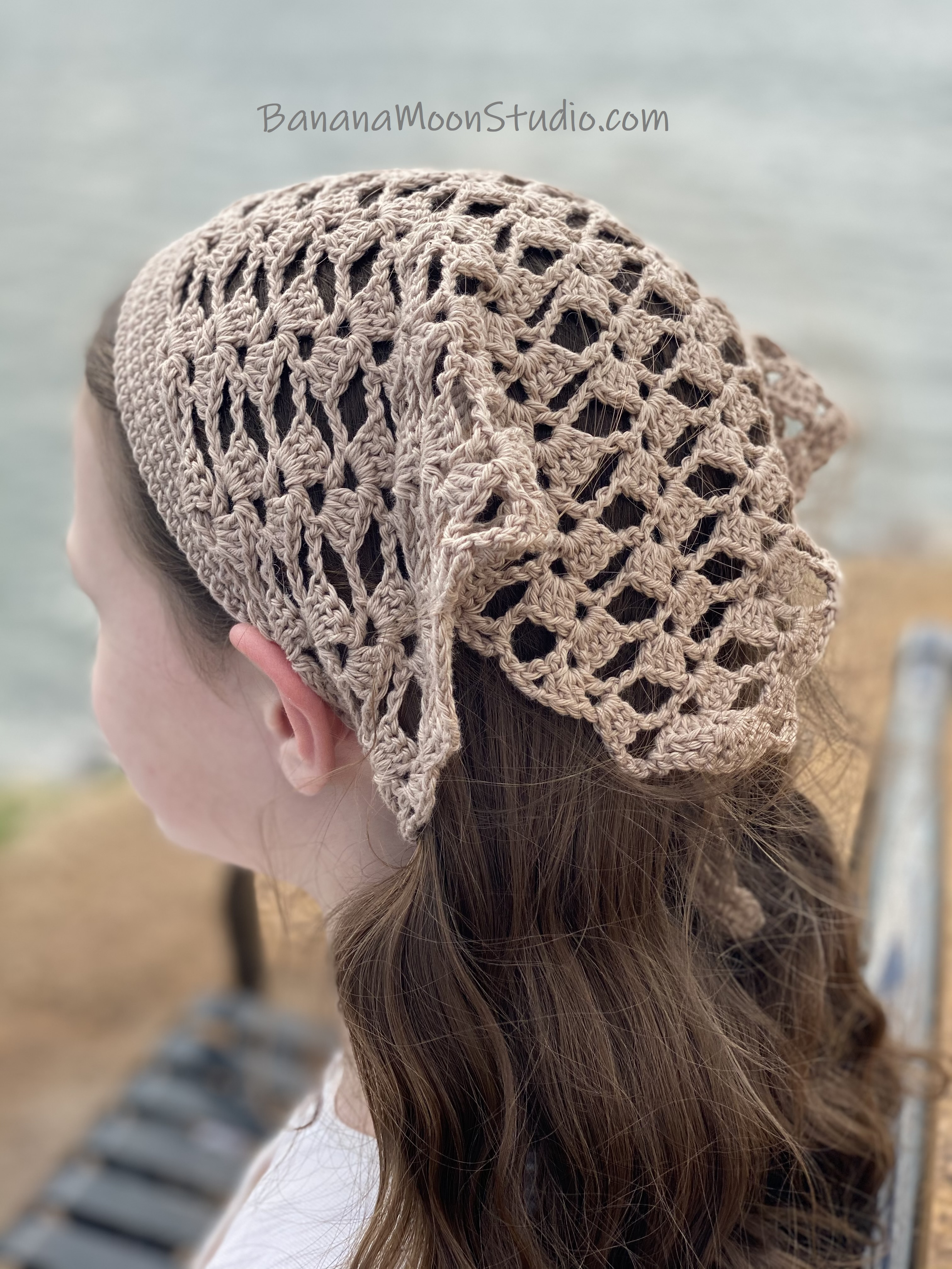 Girl wearing a crochet lace hair kerchief and sitting on a bench by the water. Text reads: BananaMoonStudio.com