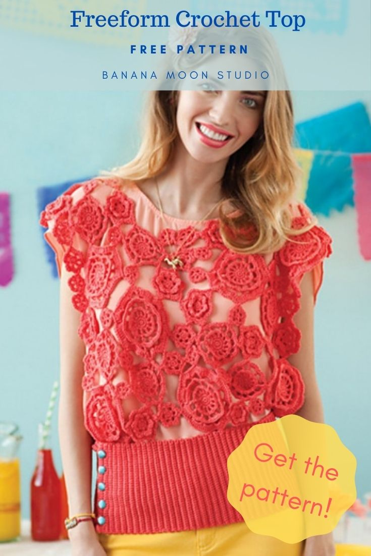 Freeform Crochet Top. Free pattern. Banana Moon Studio. Get the pattern! Woman with auburn hair and a peach carnation in her hair. Wearing a dark coral crochet blouse made of many flower motifs over a peach t-shirt. The crochet op has a wide ribbed band at the waist and blue buttons. She is wearing yellow pants. In the background there is a picnic table and a light blue wall with colorful garlands of pendants.