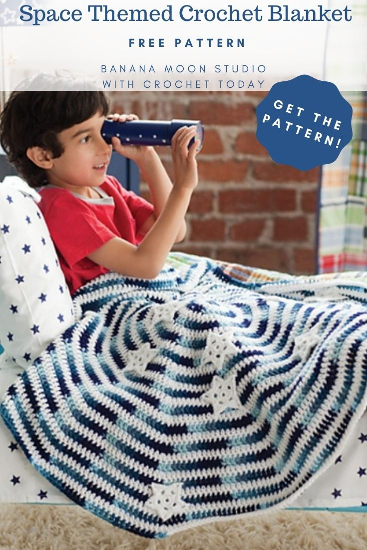 Space themed crochet blanket, free pattern, Banana Moon Studio with Crochet Today. Get the pattern! Young child sitting in a bed holding a kaleidoscope. Bed has white sheet and pillowcase with blue stars. In his lap is a crochet blanket designed to look like a galaxy. Spiraled white with shades of blue with crochet applique stars.