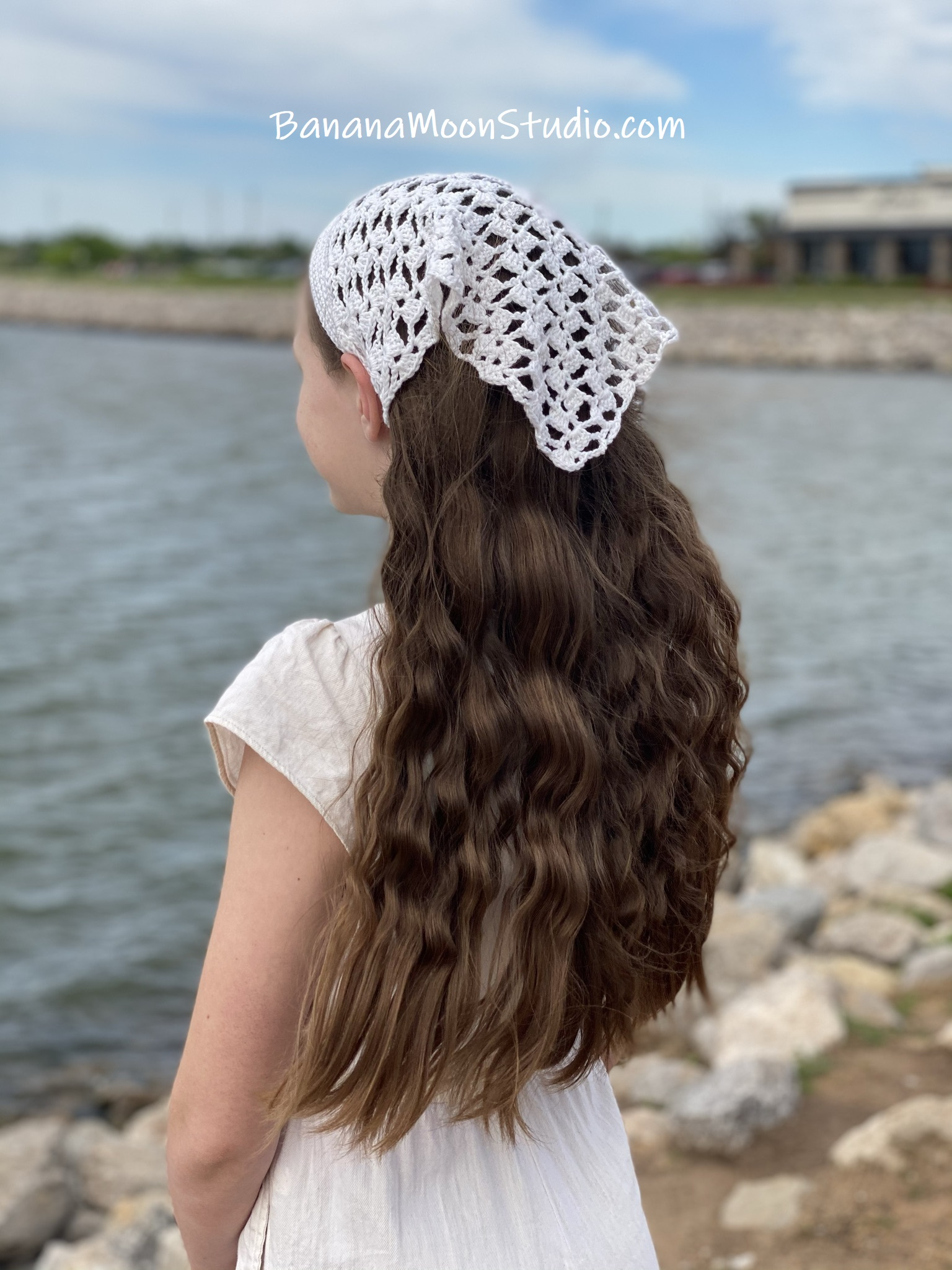 Girl standing near the water wearing a white lace hair kerchief and white jumpsuit. Marietta Kerchief free lacy crochet kerchief pattern from Banana Moon Studio.