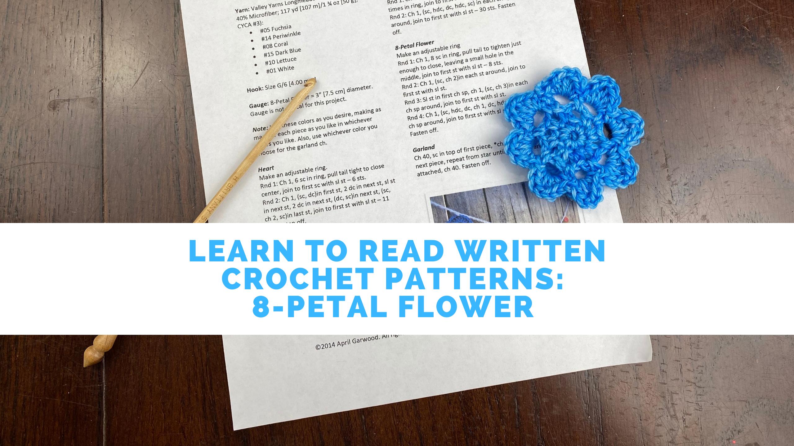 Printed crochet pattern, wooden crochet hook, and a blue crochet flower sitting on a table. Text reads: Learn to read written crochet patterns: 8-petal flower.