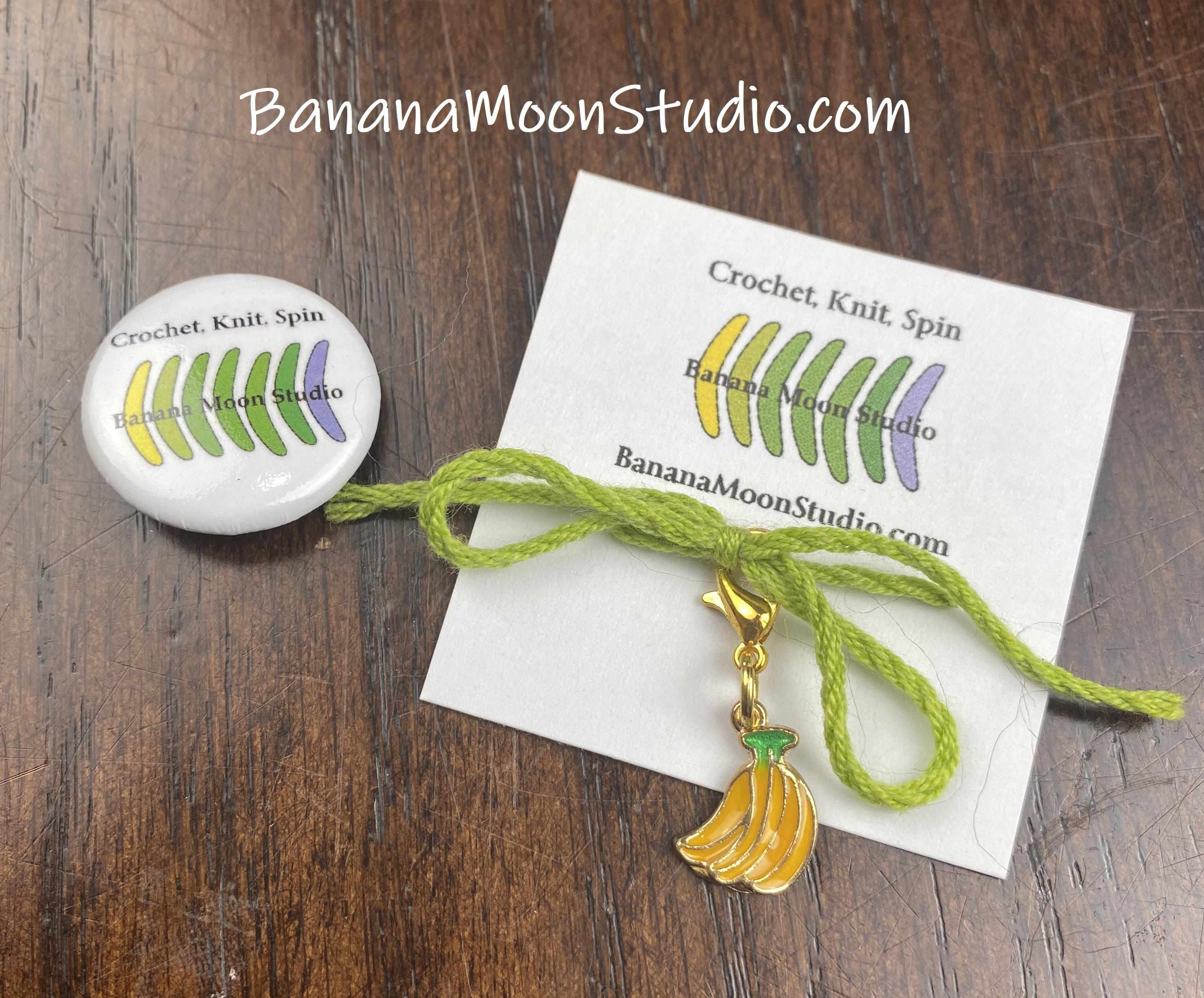 Small round pin with Banana Moon Studio logo. Small card with a Banana Moon Studio logo, a bow made of green yarn, and a bunch of bananas stitch marker attached to it. Wooden table in the background. Text reads: BananaMoonStudio.com/ Crochet, knit, spin.