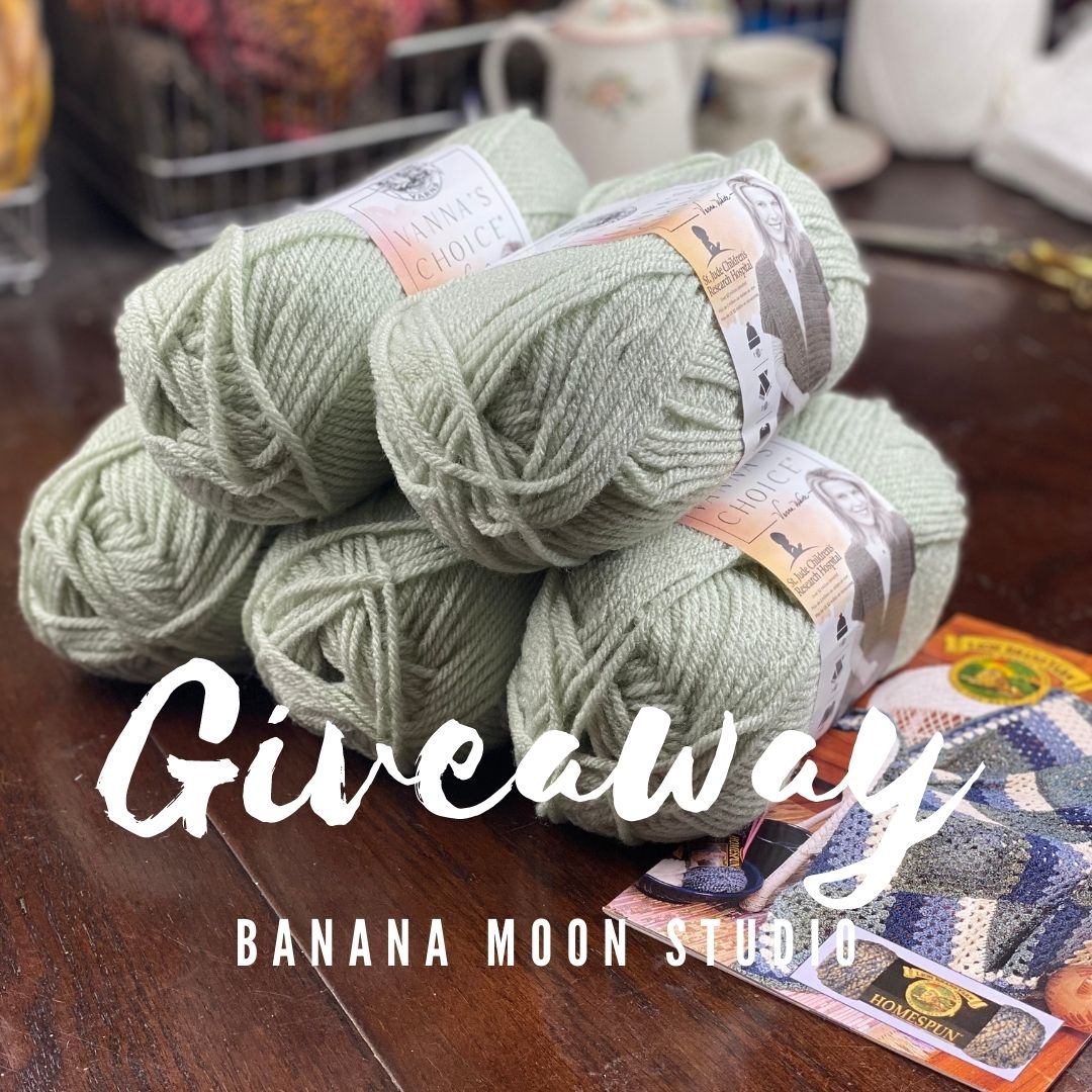 5 skeins of pale green yarn and a pattern booklet on a table with various items in the background. Text reads: Giveaway. Banana Moon Studio.