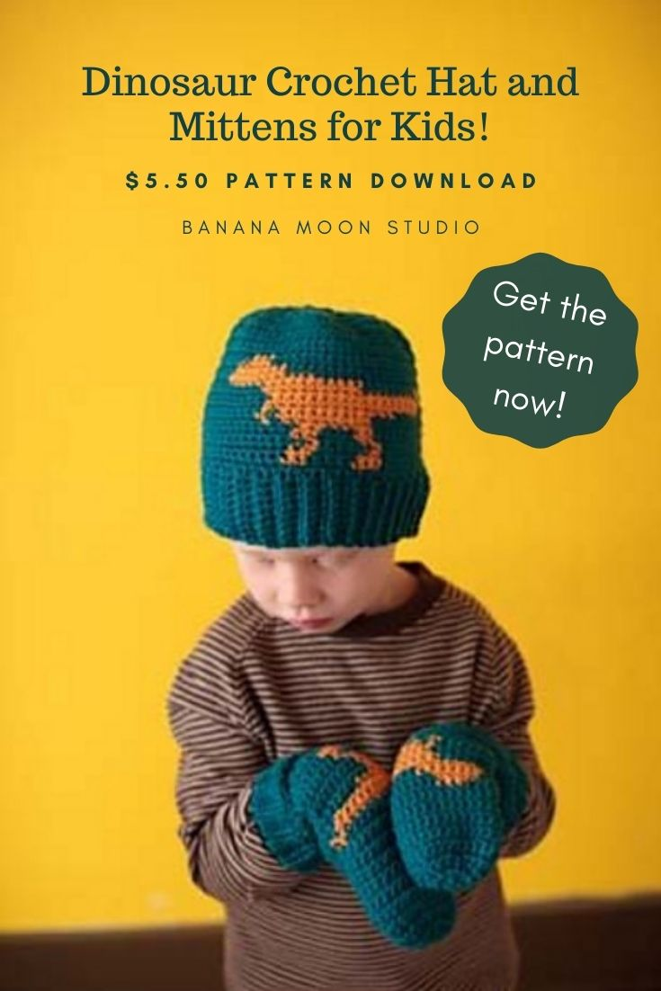 Yellow background. Child wearing a crochet hat and mittens that are teal with an orange dinosaur on them. Text reads: Dinosaur Crochet Hat and Mittens for Kids! $5.50 Pattern Download. Banana Moon Studio. Get the pattern now!