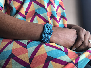 Person wearing a bright print top, wearing a blue braided crochet bracelet.