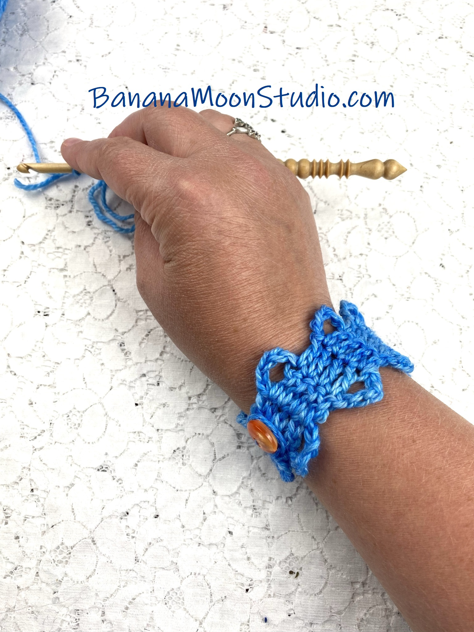 Hand and forearm wearing a blue crochet bracelet on a white lace background. Text reads: BananaMoonStudio.com