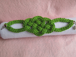 Green crochet bracelet made of crochet cord tied in an intricate, loose, decorative knot. The bracelet is on a white cushion on a pink background.