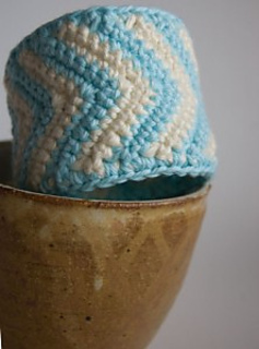 Light blue and white chevron crochet cuff bracelet sitting on the edge of a brown bowl with a white background.